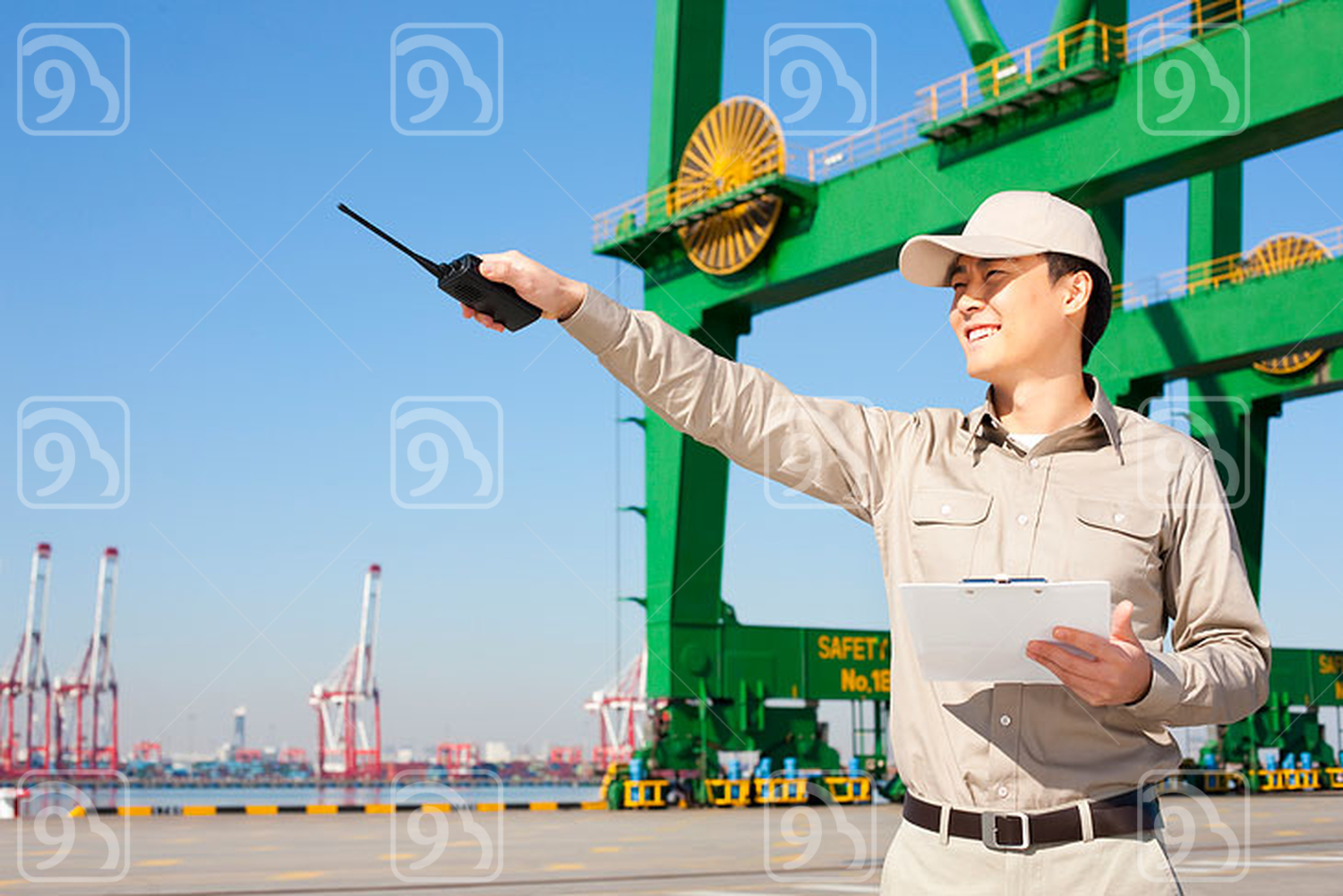 Male Chinese shipping industry worker with walkie-talkie pointing