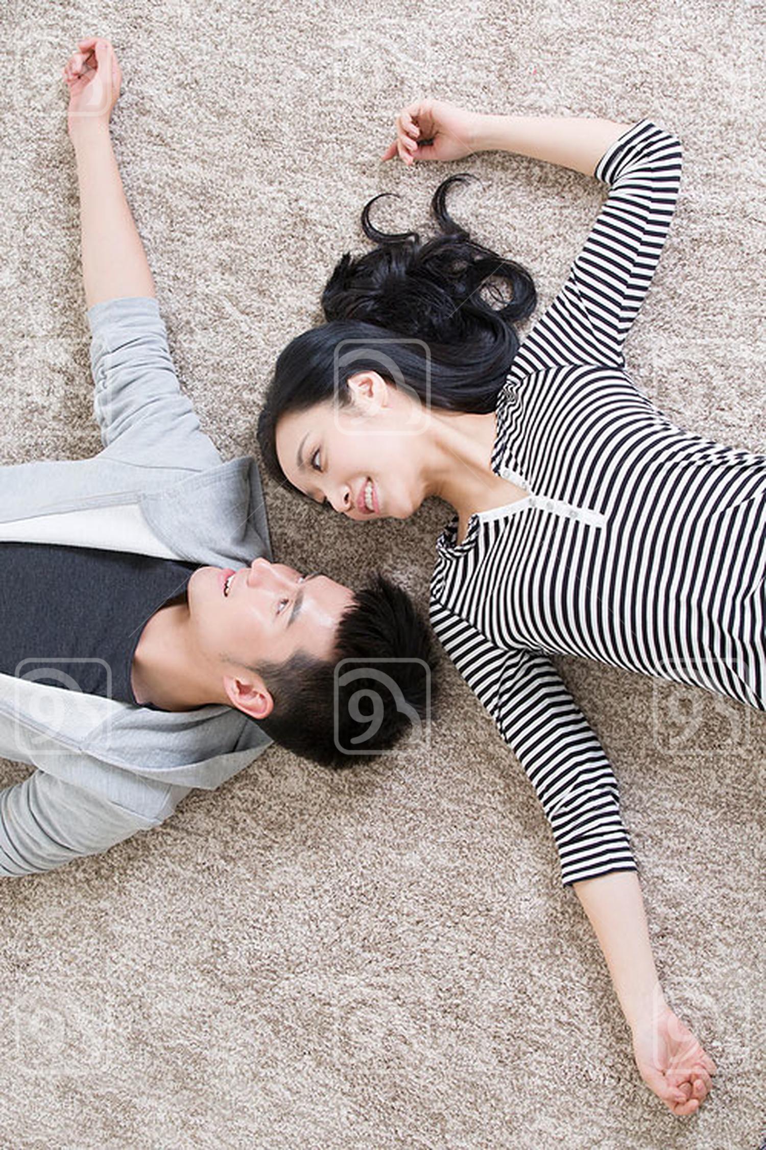 Young Chinese couple lying on floor