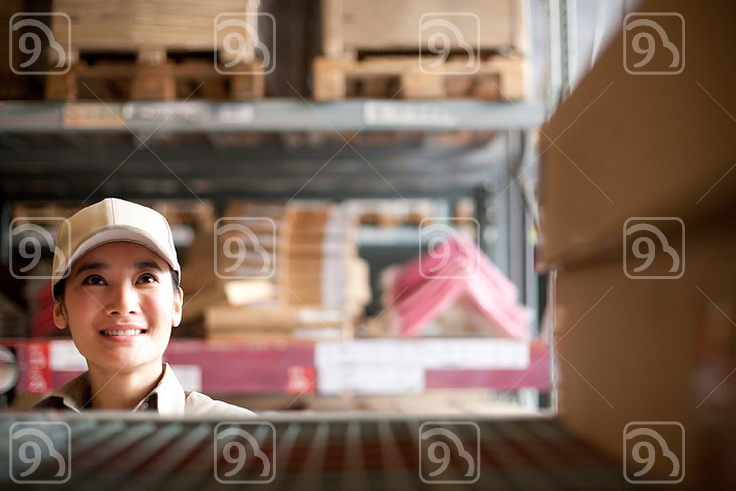 Female Chinese warehouse worker looking at boxes