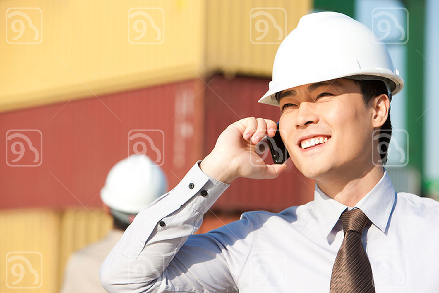 Chinese businessman on his cellphone with cargo containers in the background