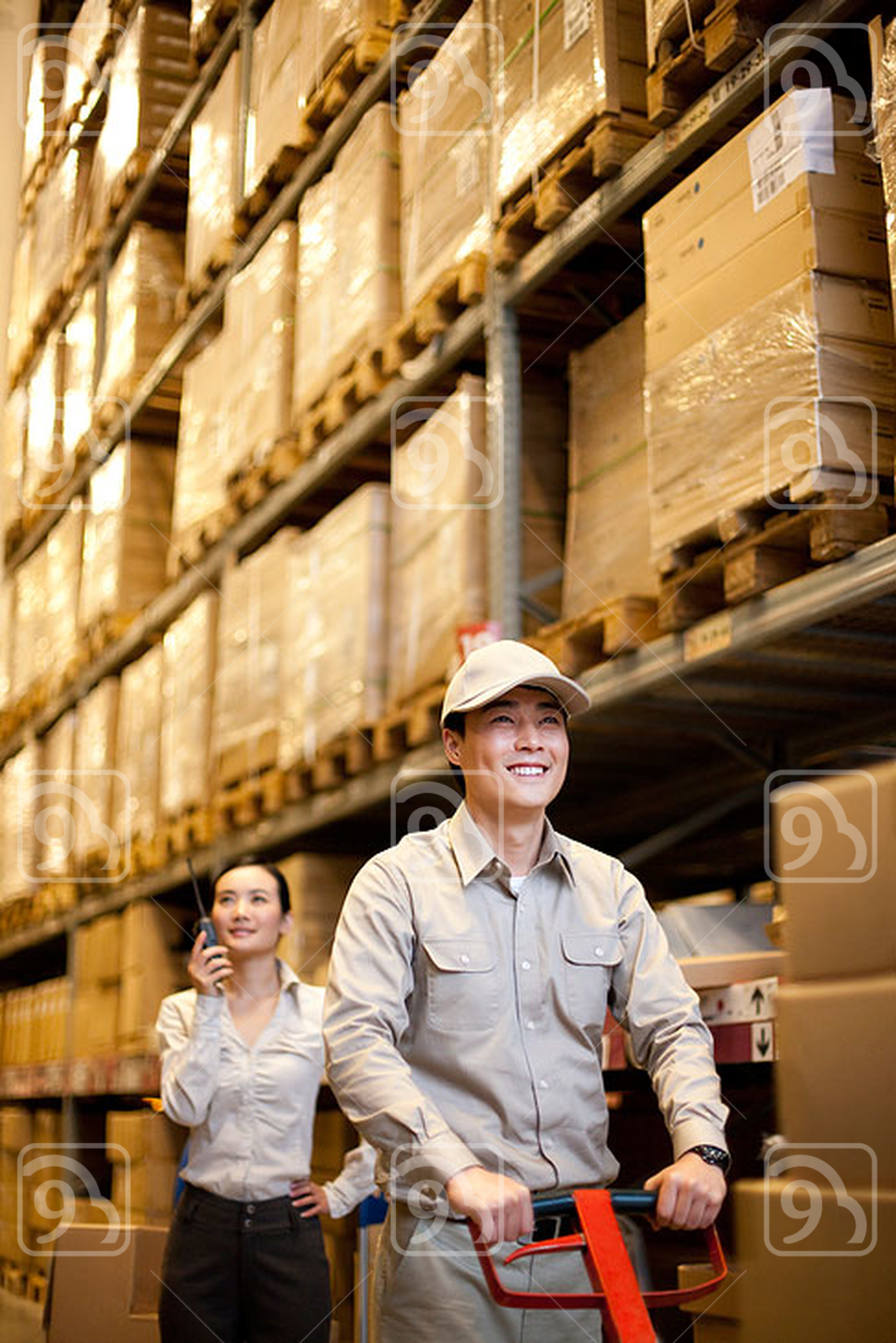 Male Chinese warehouse with Chinese businesswoman in the background