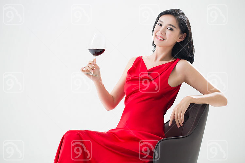 Elegant young Chinese woman enjoying red wine