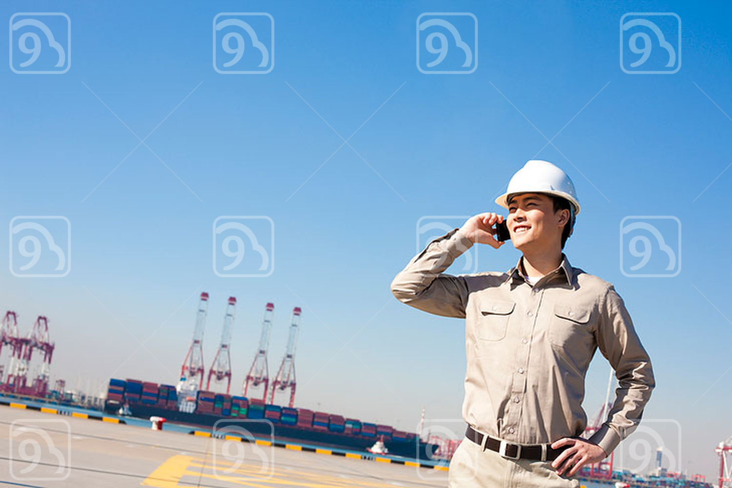 Male Chinese shipping industry worker on the phone with shipping dock background