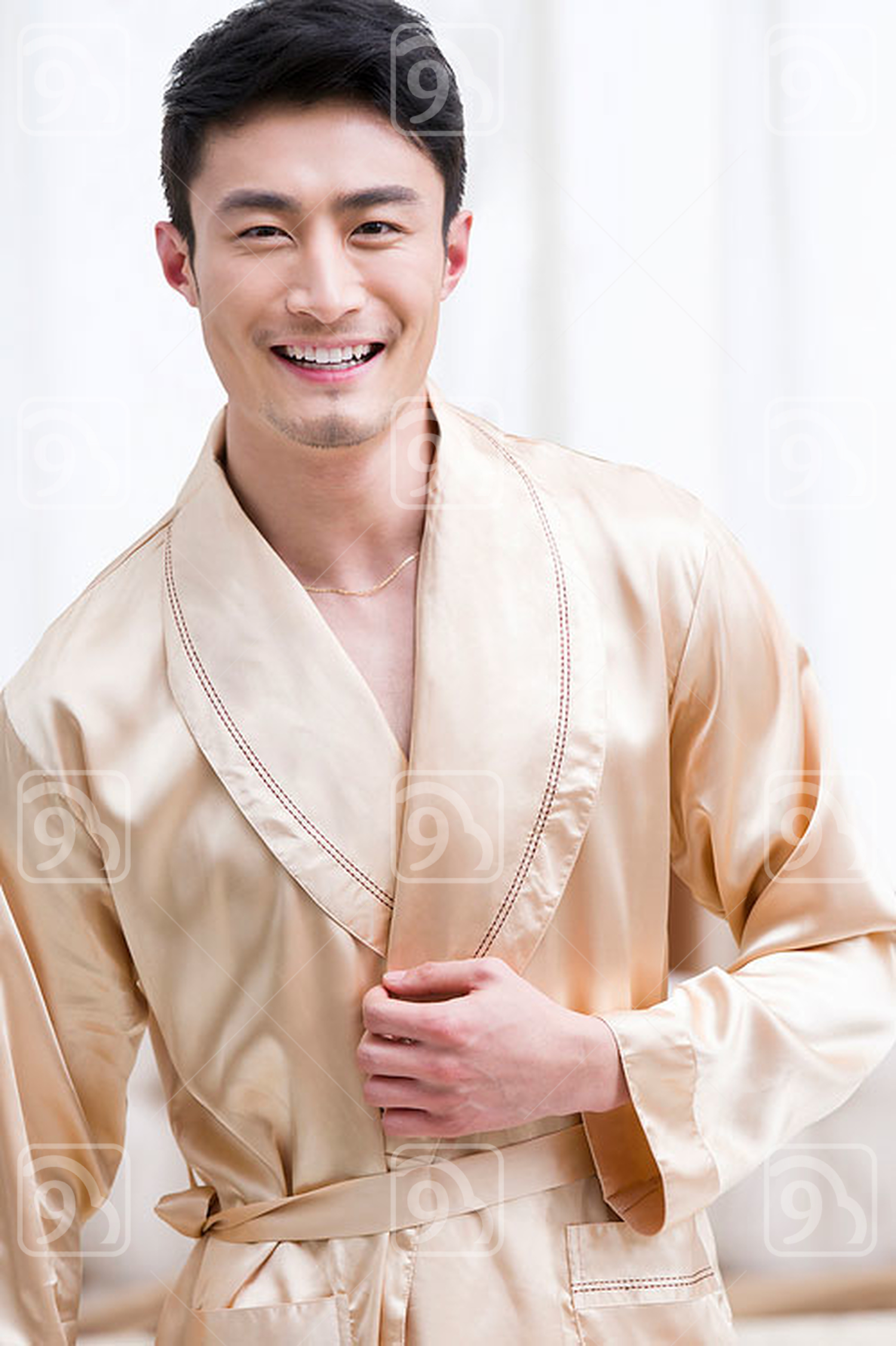 Cheerful young Chinese man in bedroom