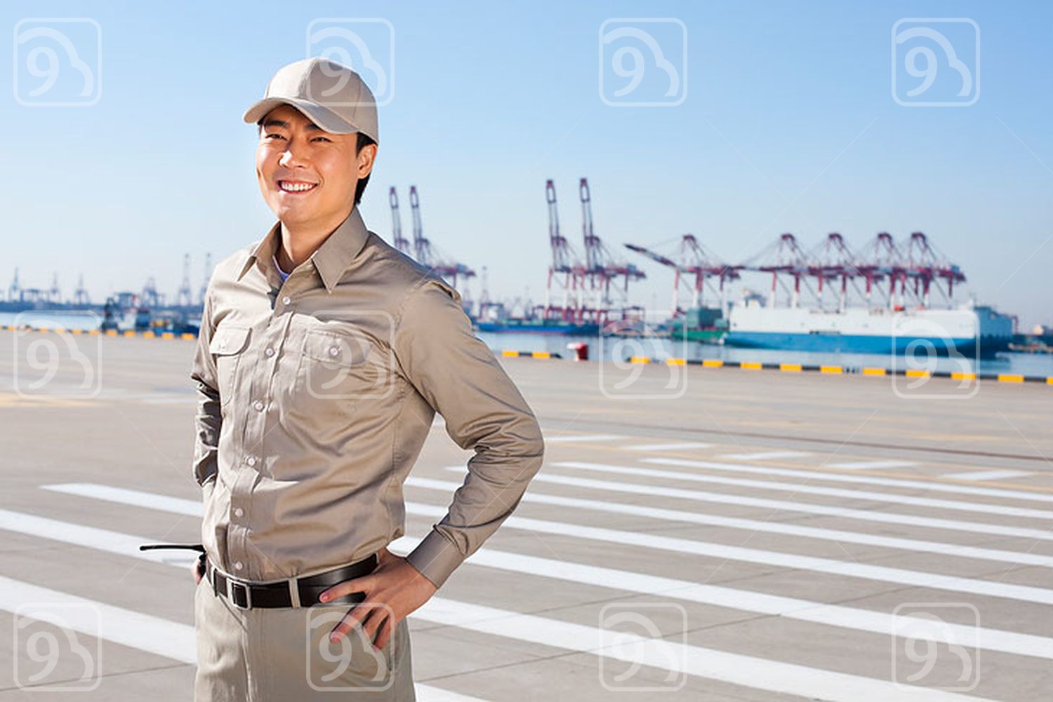 Male Chinese shipping industry worker with shipping dock background