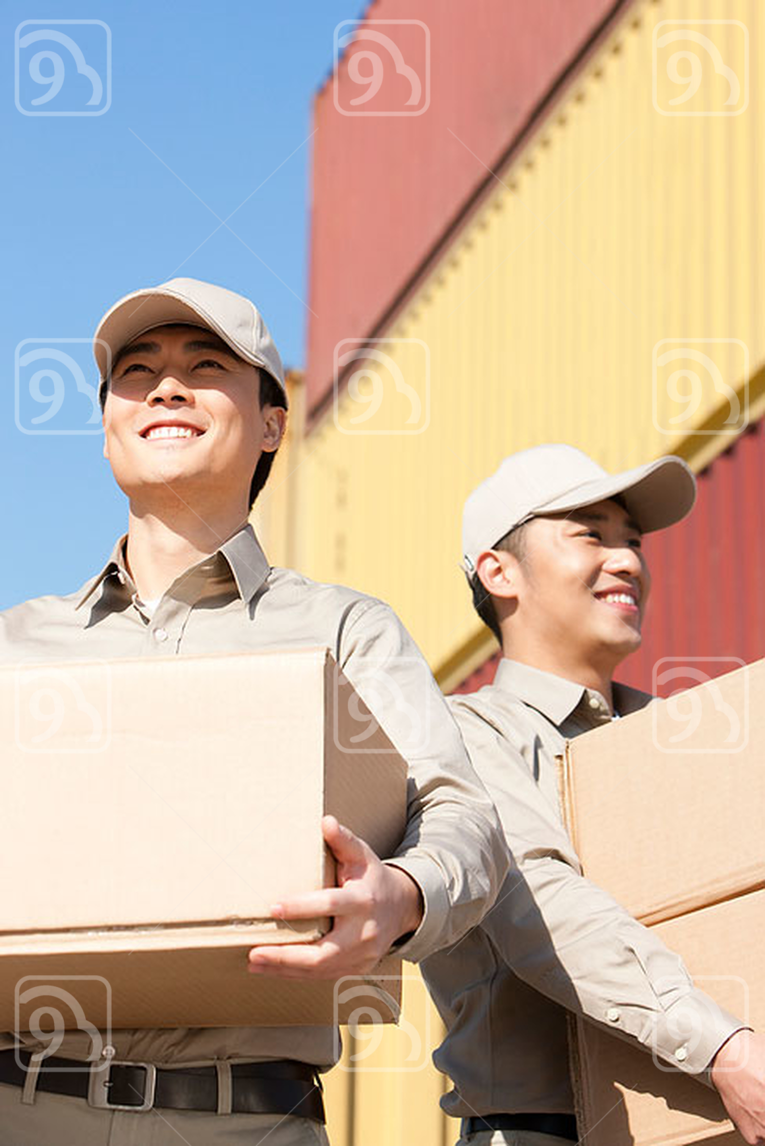 Chinese shipping industry workers carrying cardboard boxes