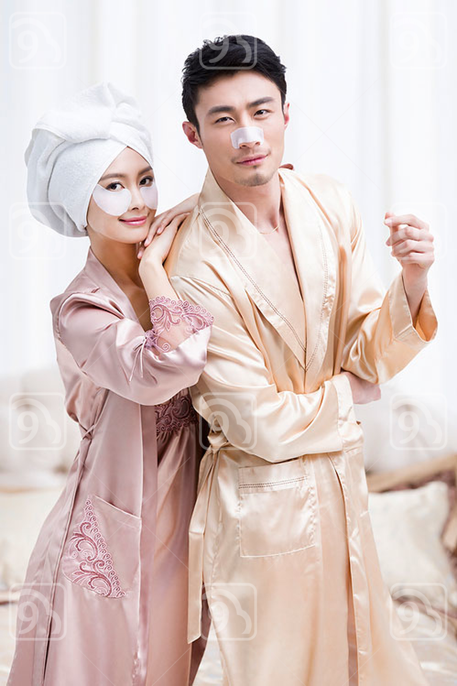 Young Chinese couple applying facial masks