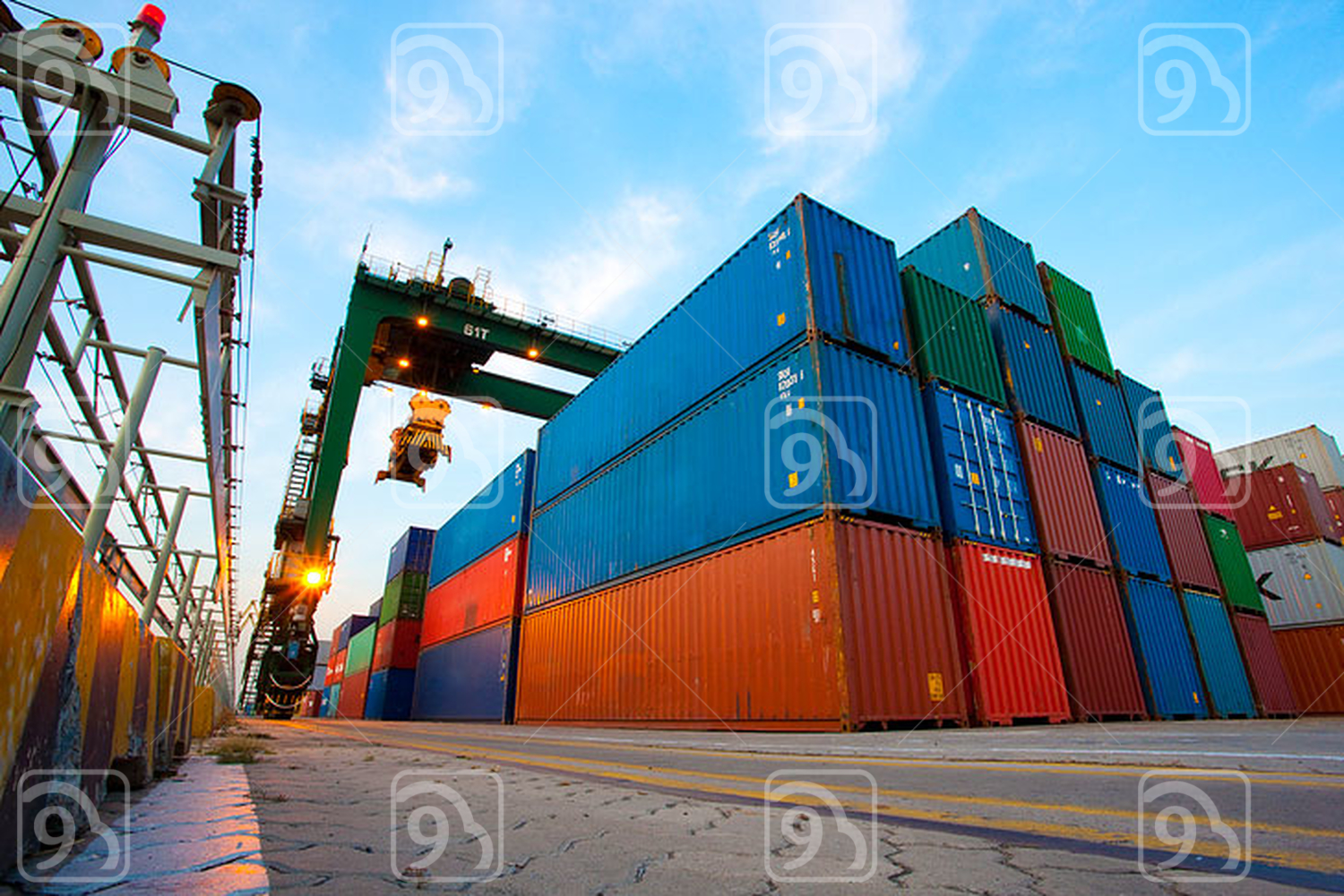 Cranes and multi-colored stack of cargo containers at dusk