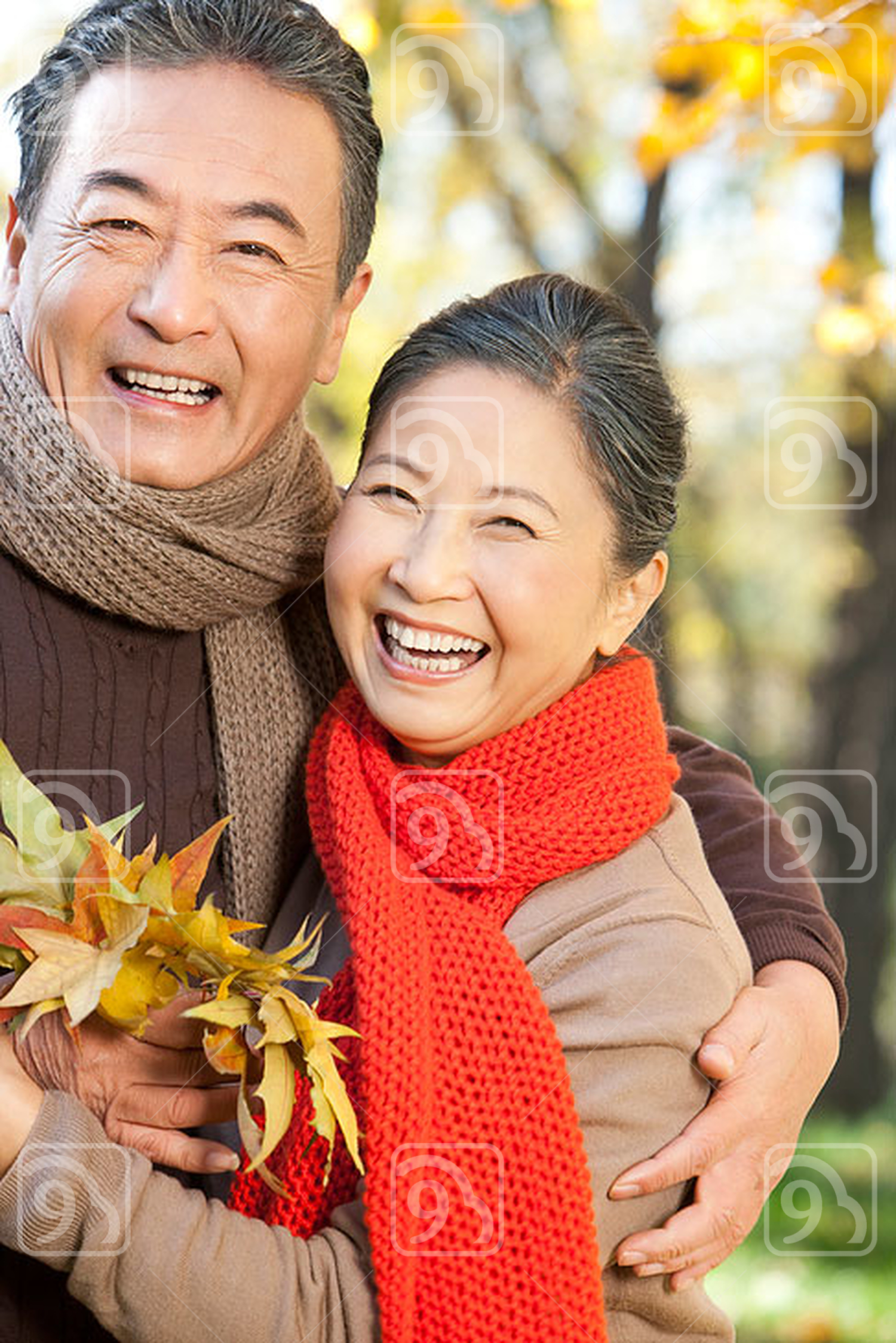 Senior Chinese couple with a collection of leaves in autumn