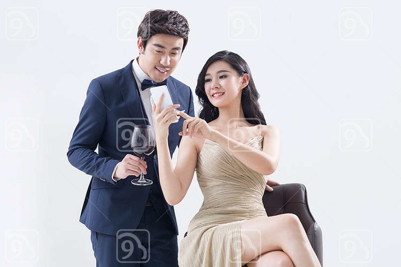 Elegant young Chinese couple using smart phone