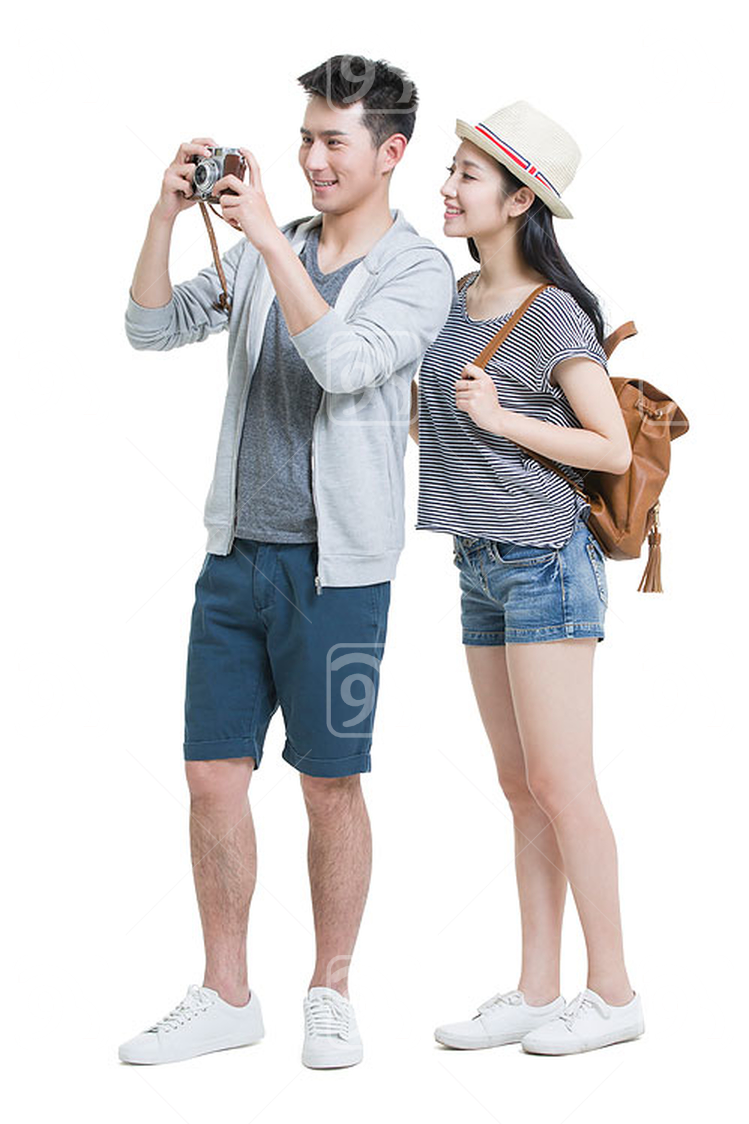 Happy young Chinese couple traveling with camera