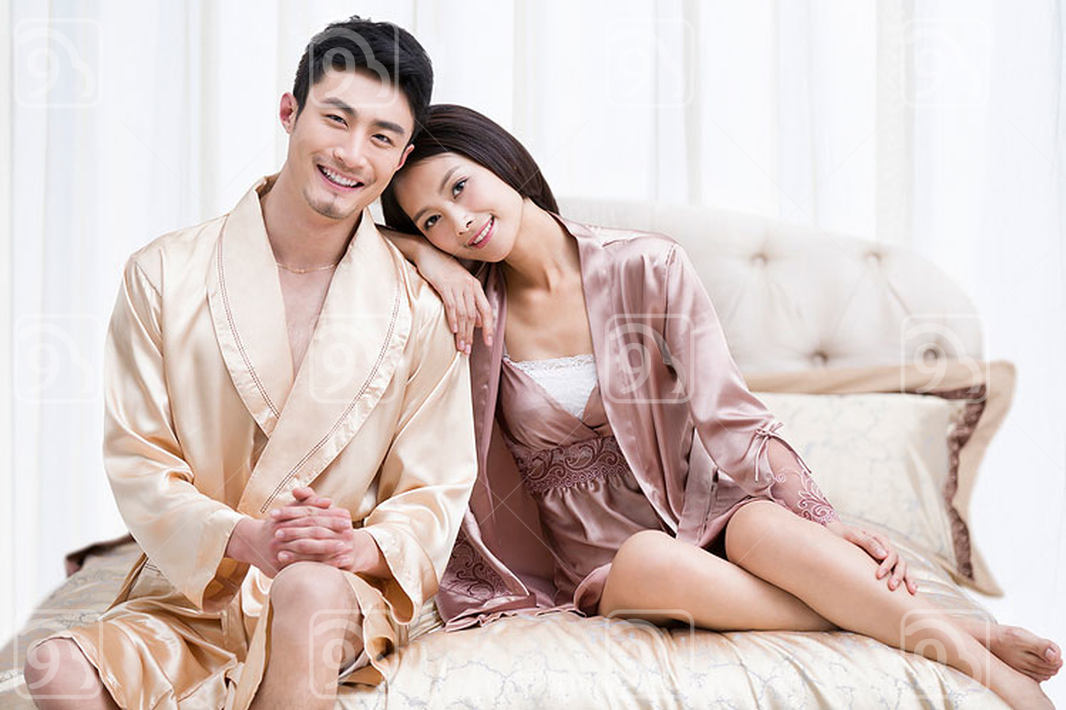 Happy young Chinese couple in bedroom