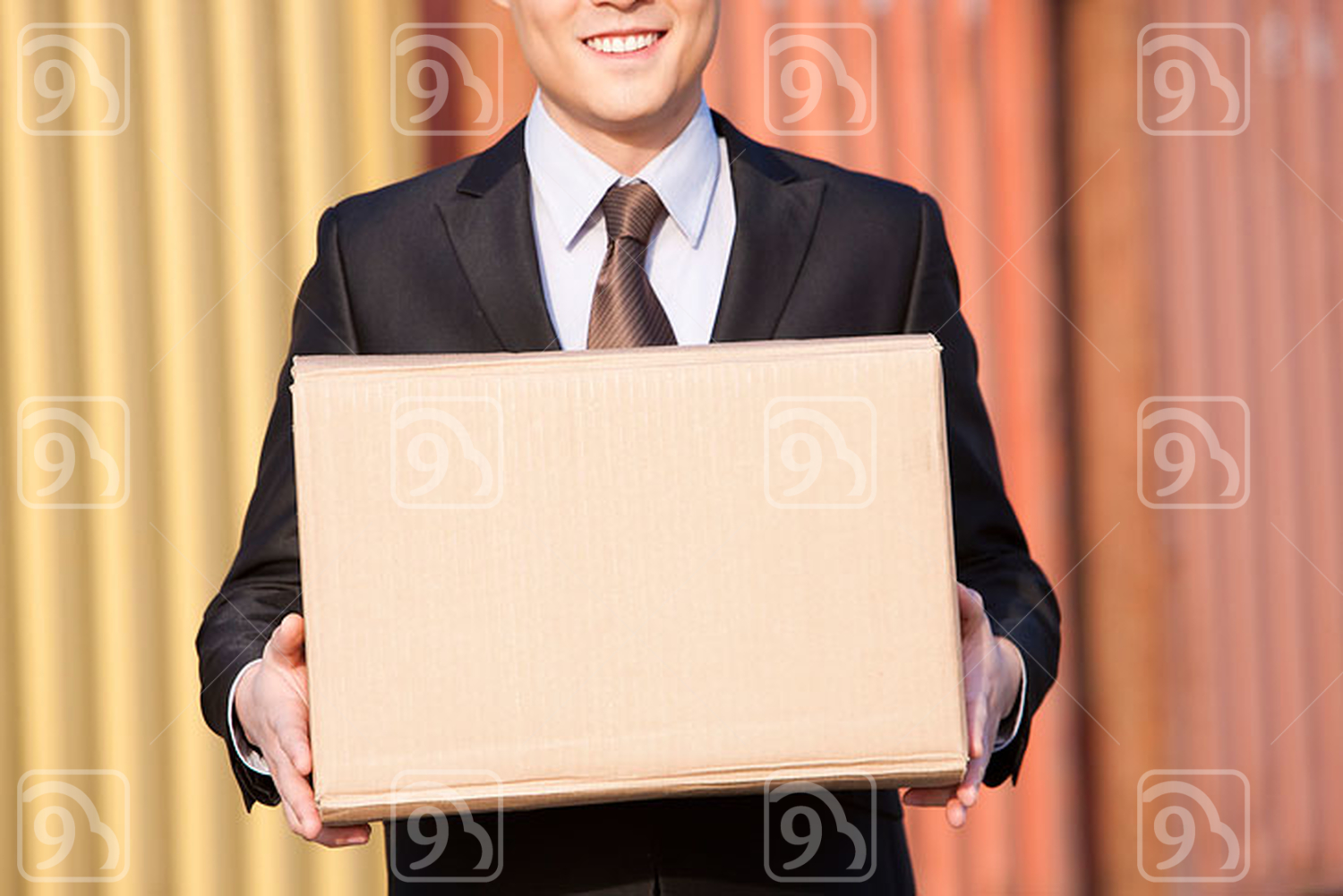 Chinese businessman carrying a cardboard box with cargo containers in the background