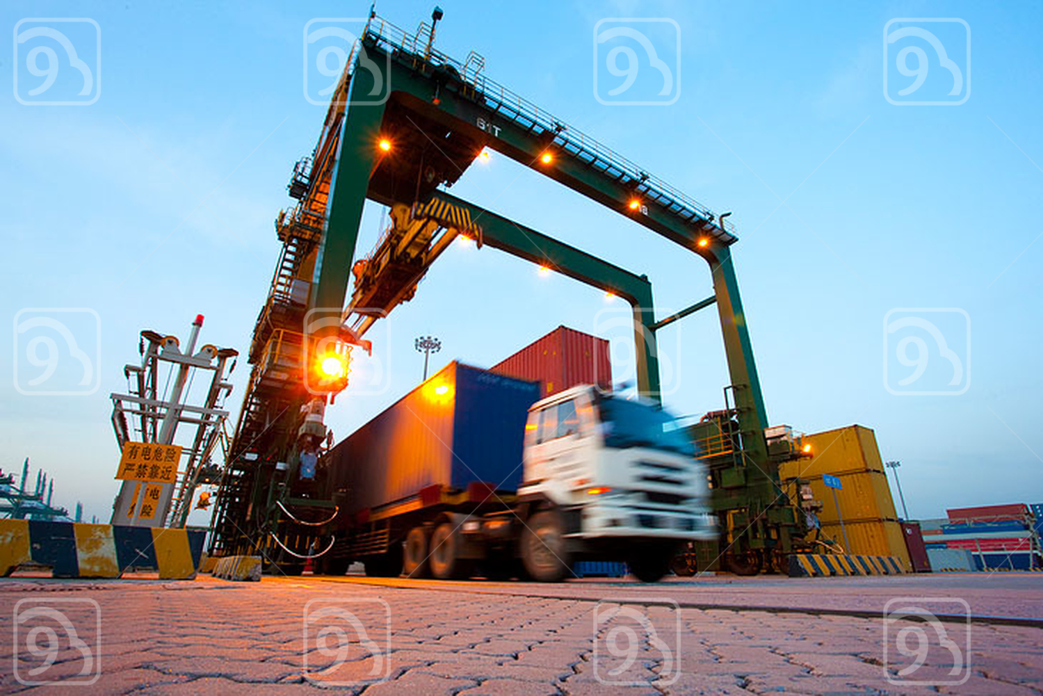 Blurred motion of truck with cargo containers and cranes in a shipping port