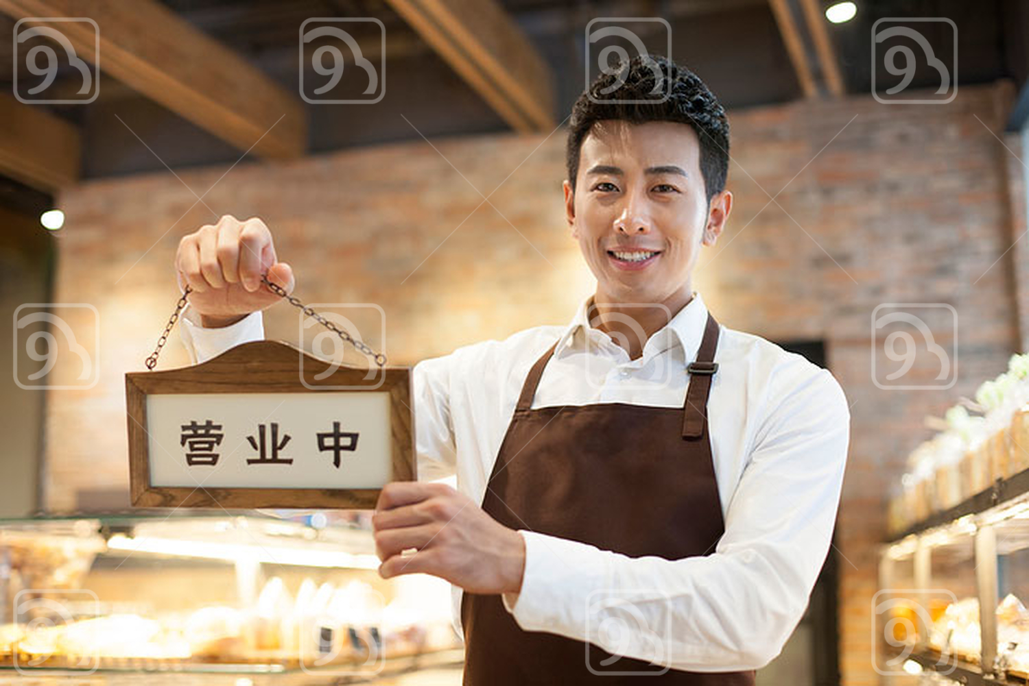 Young Chinese man holding an open sign