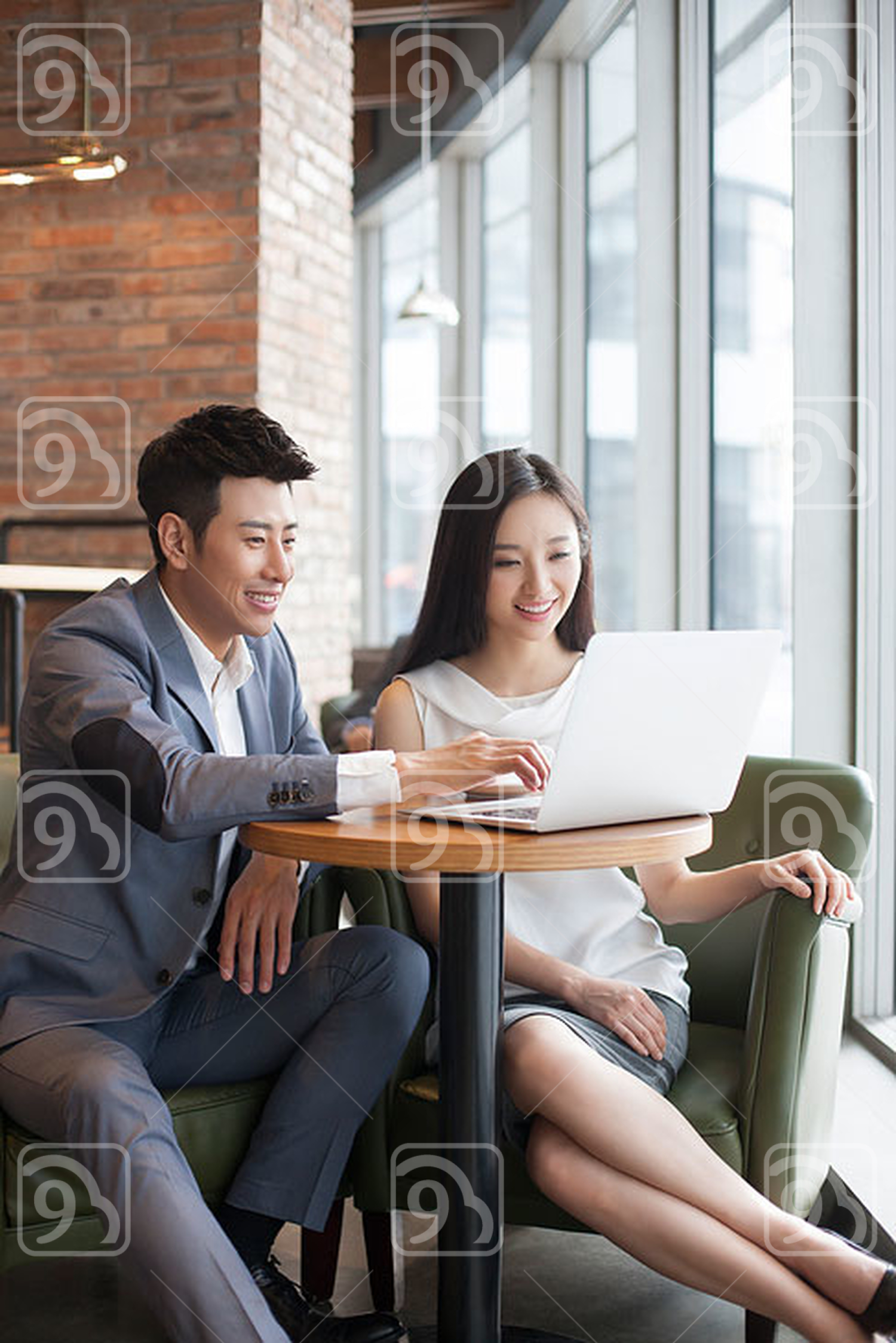 Chinese businesswoman and businessman working with laptop in café