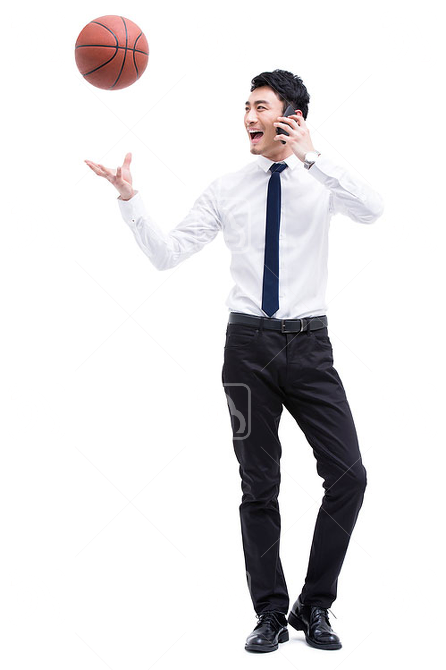 Young Chinese businessman on the phone with a tossing basketball in air