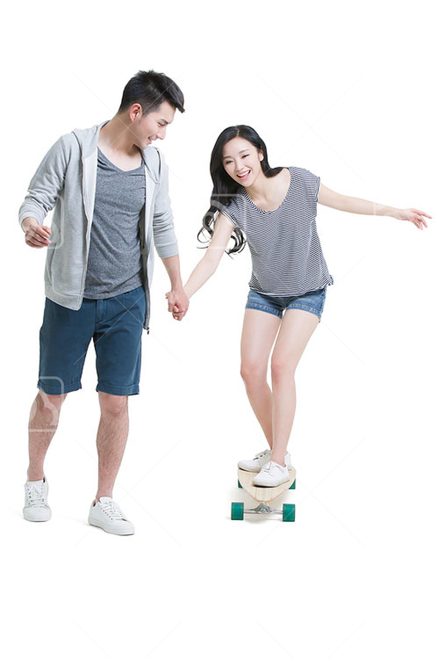 Young Chinese man teaching girlfriend to skateboard