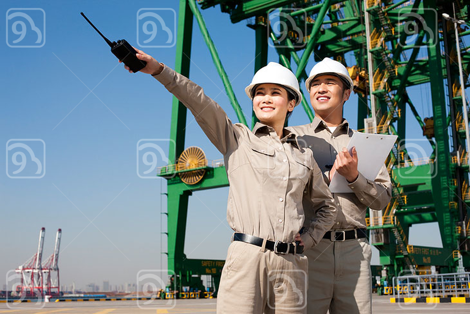 Chinese shipping industry workers pointing with walkie-talkie