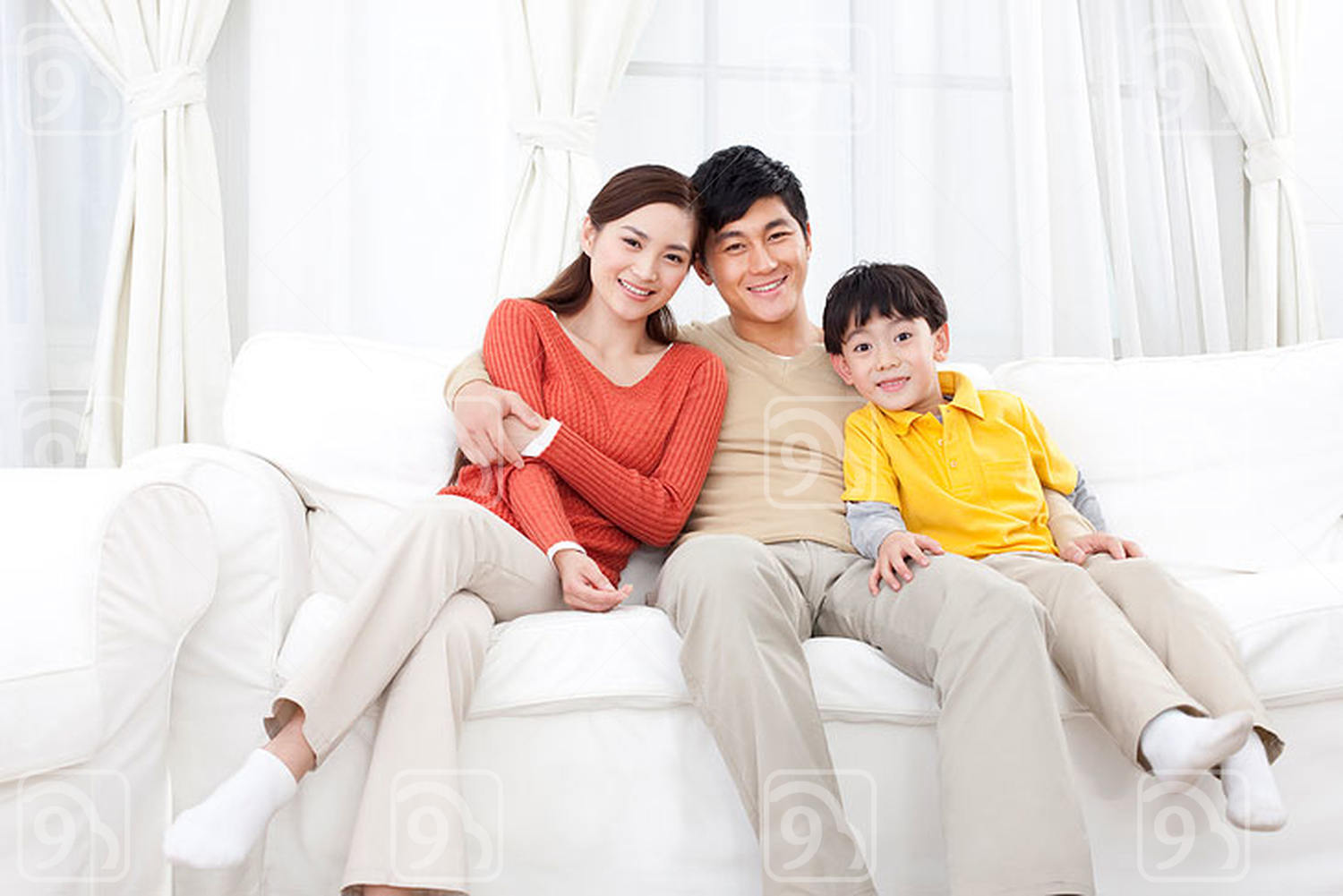 Happy Chinese family sitting in couch