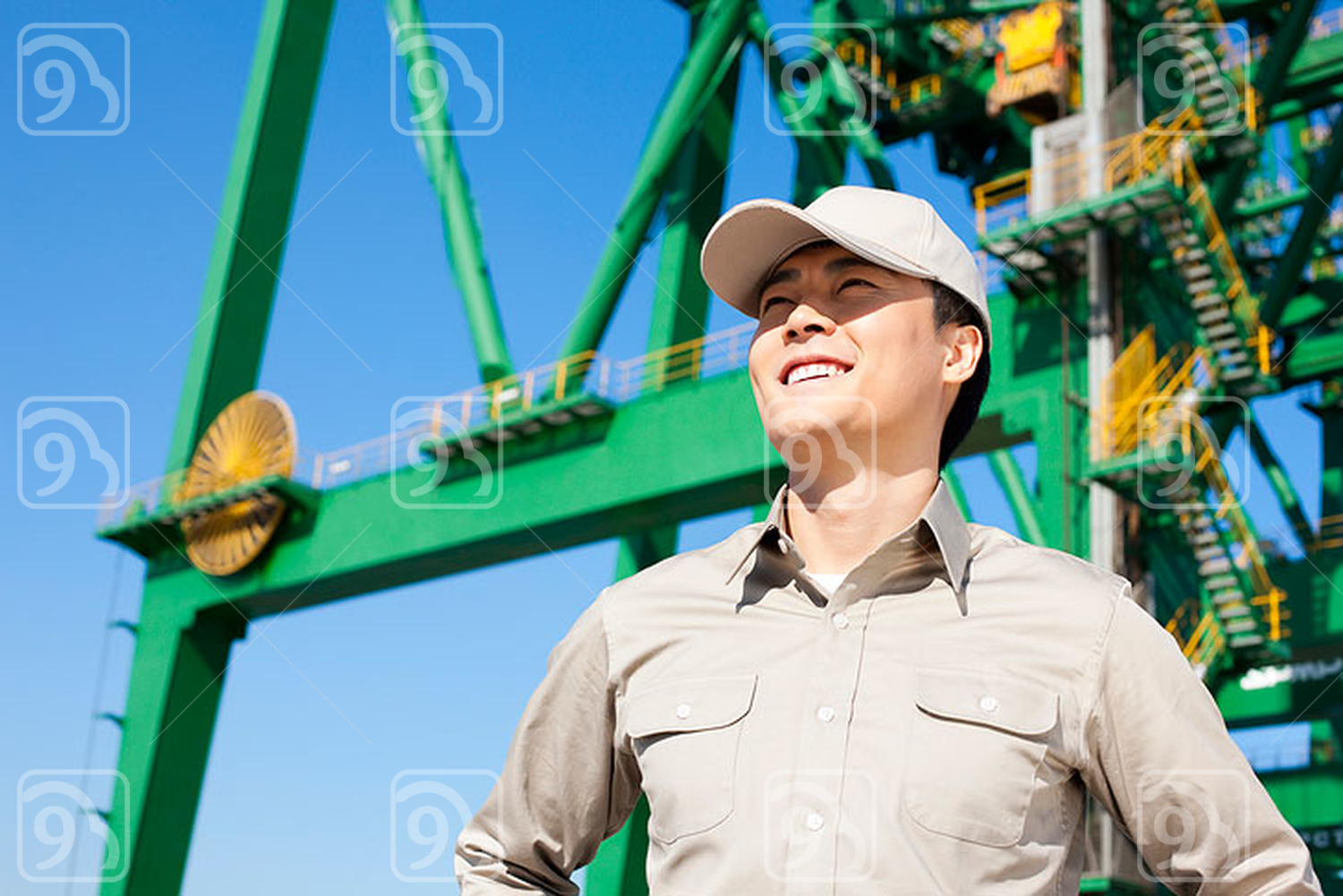 Male Chinese shipping industry worker with crane in the background