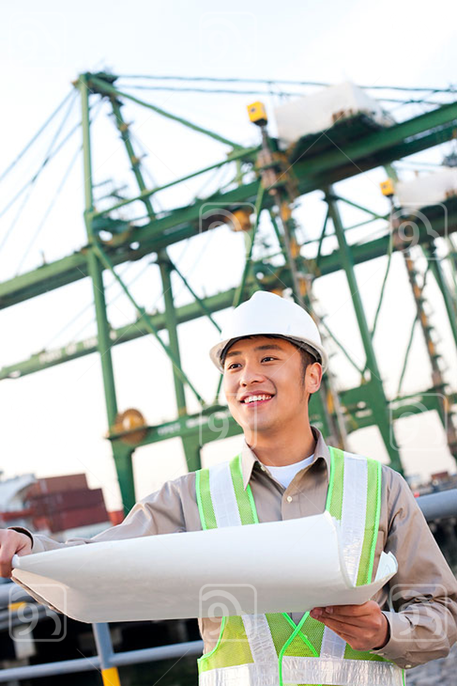 Chinese shipping industry worker looking over blueprints