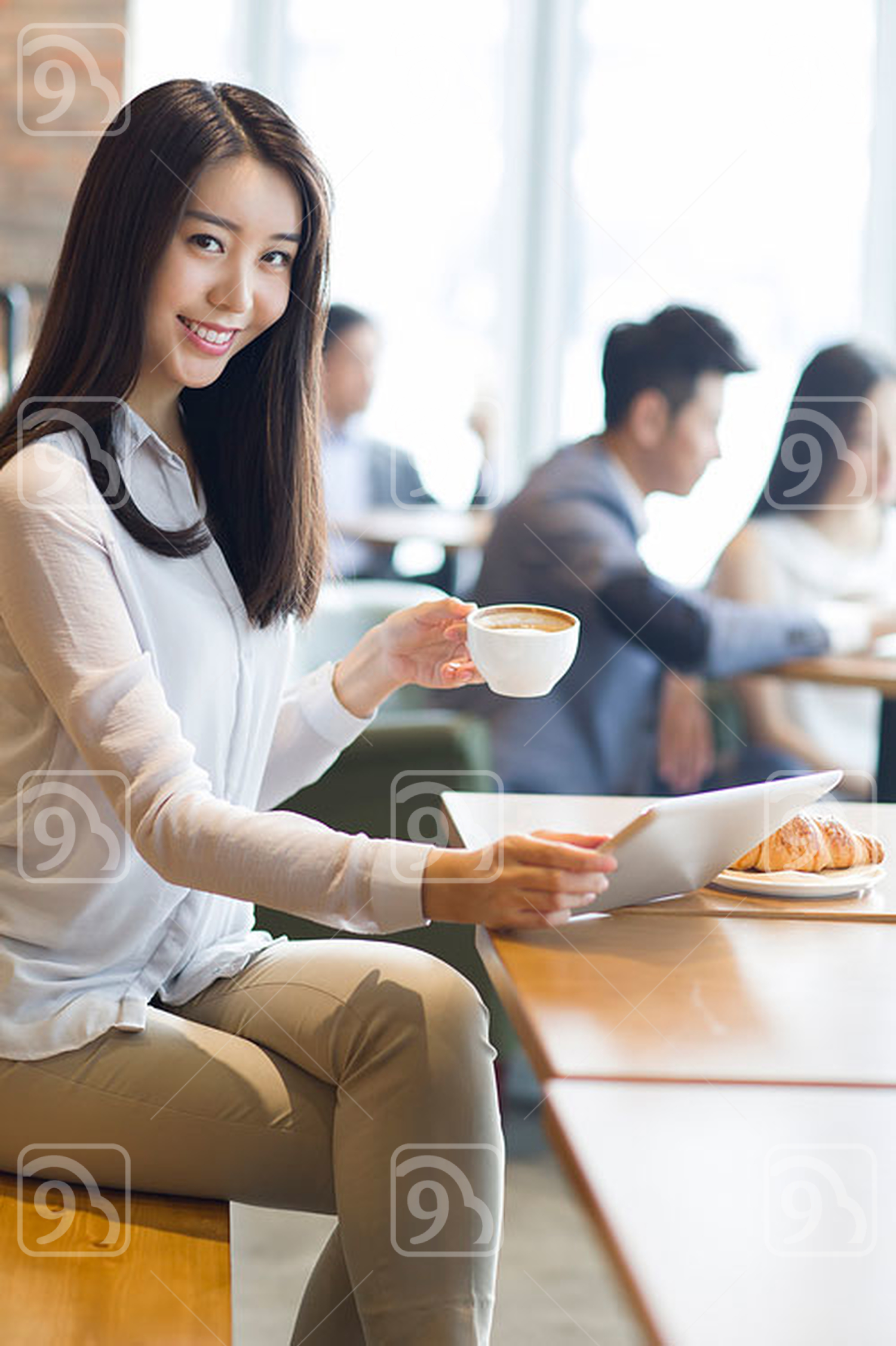 Young Chinese woman using digital tablet in café
