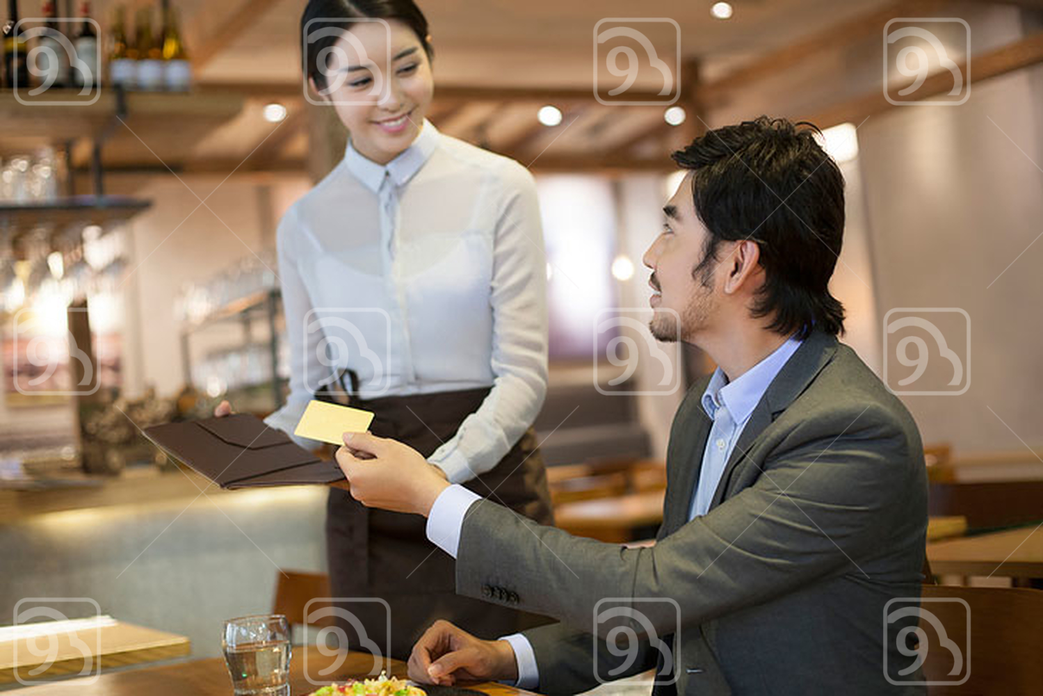 Chinese businessman paying bill by credit card in restaurant