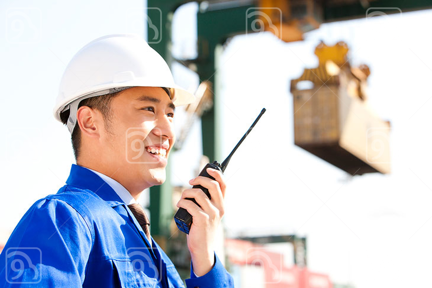 Chinese shipping industry manager directing cranes with his walkie-talkie