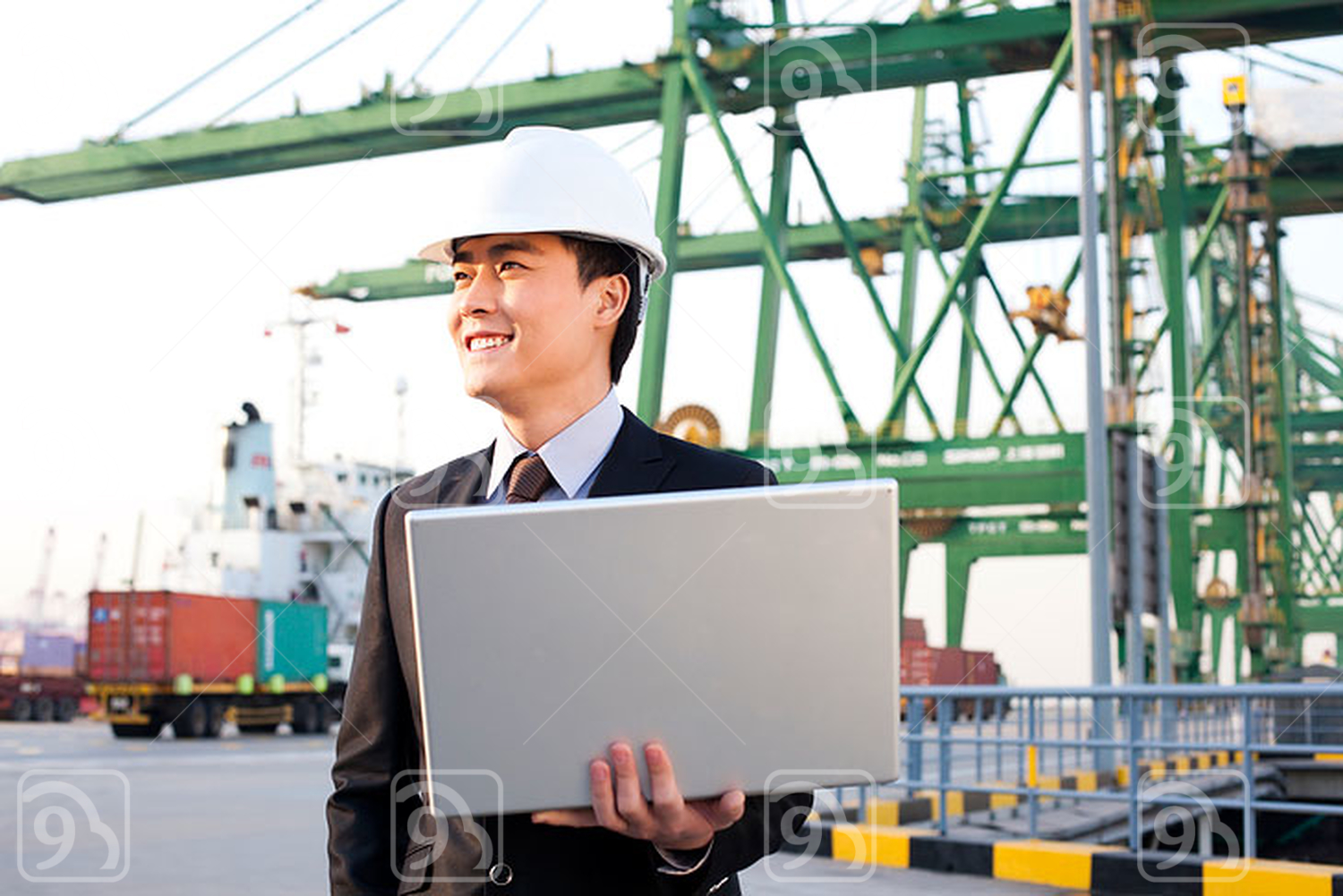 Chinese businessman using a laptop at a shipping port