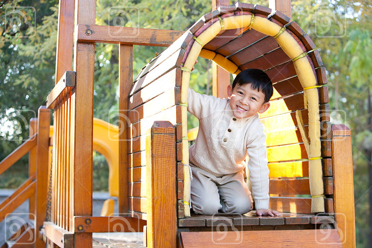 Chinese boy crawling through tunnel in playground