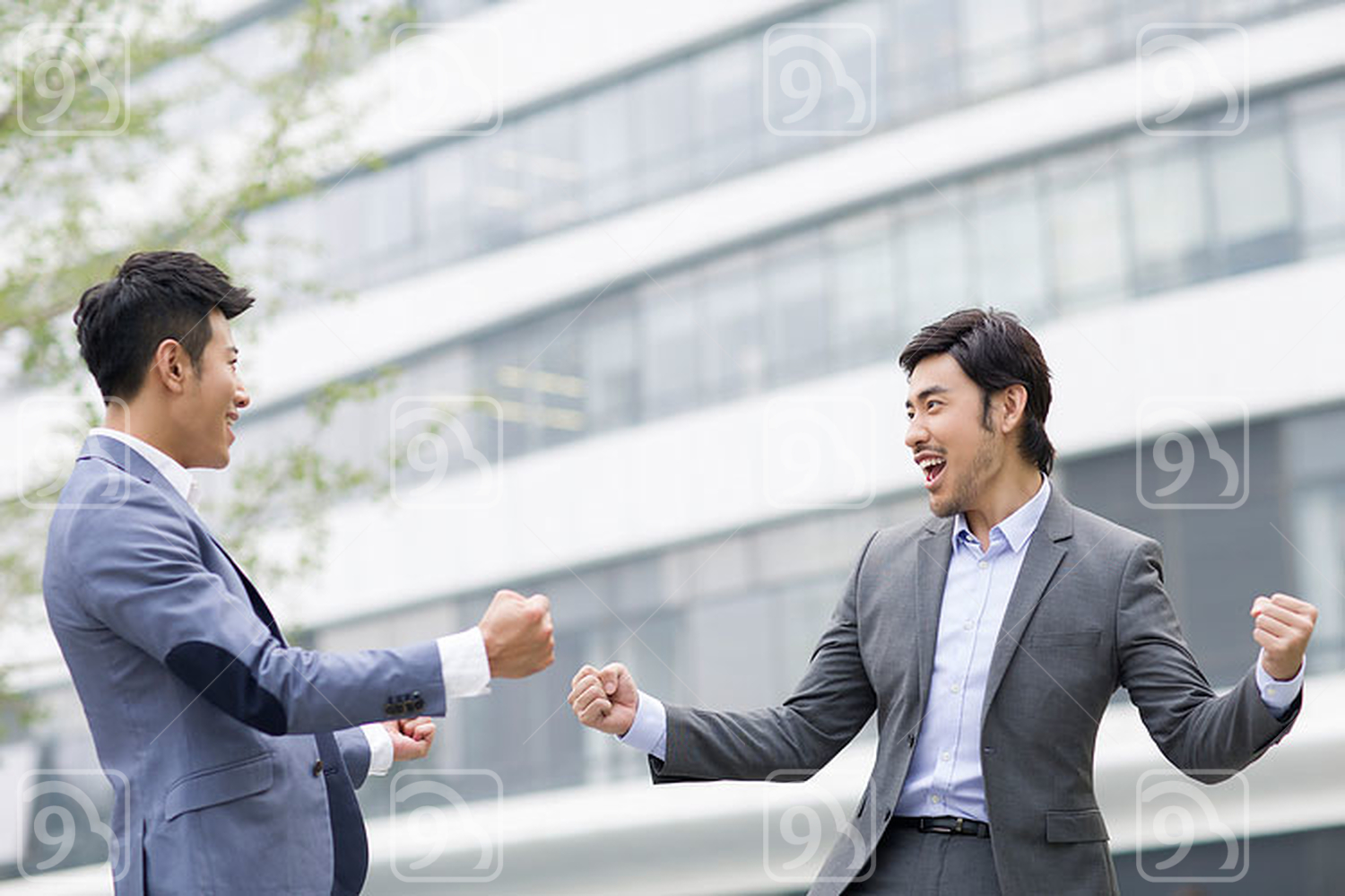 Happy Chinese businessmen punching the air