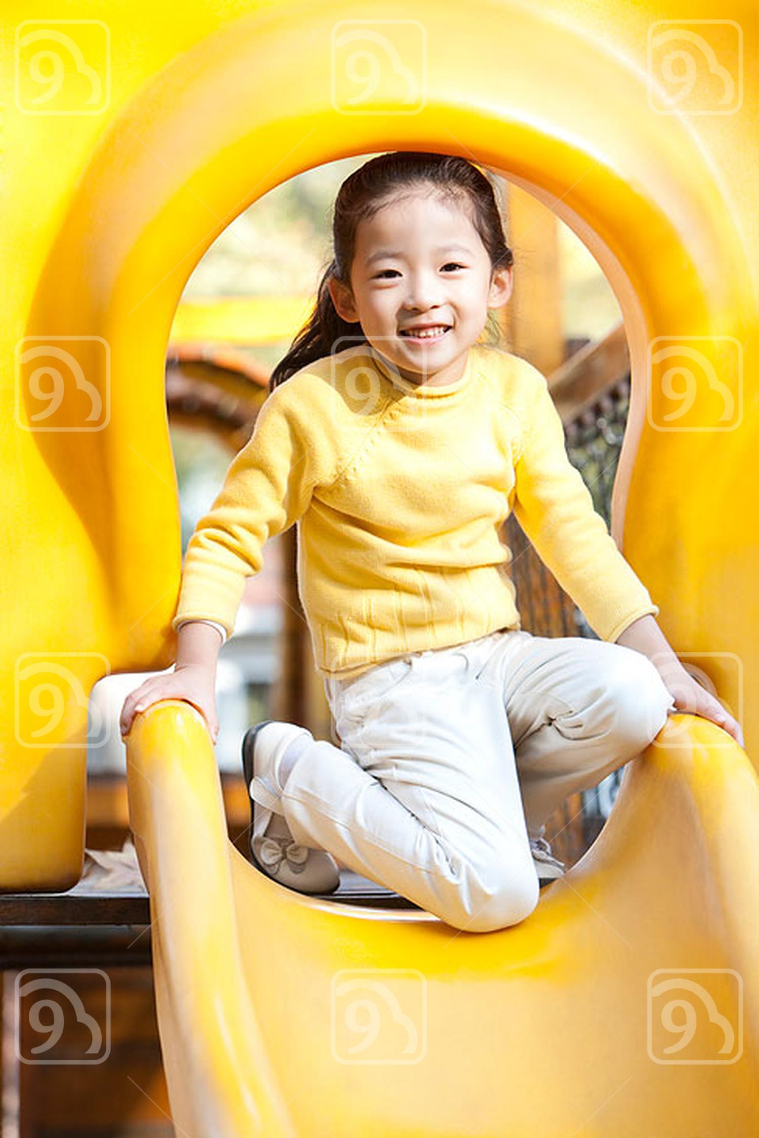 Chinese girl playing on playground slide