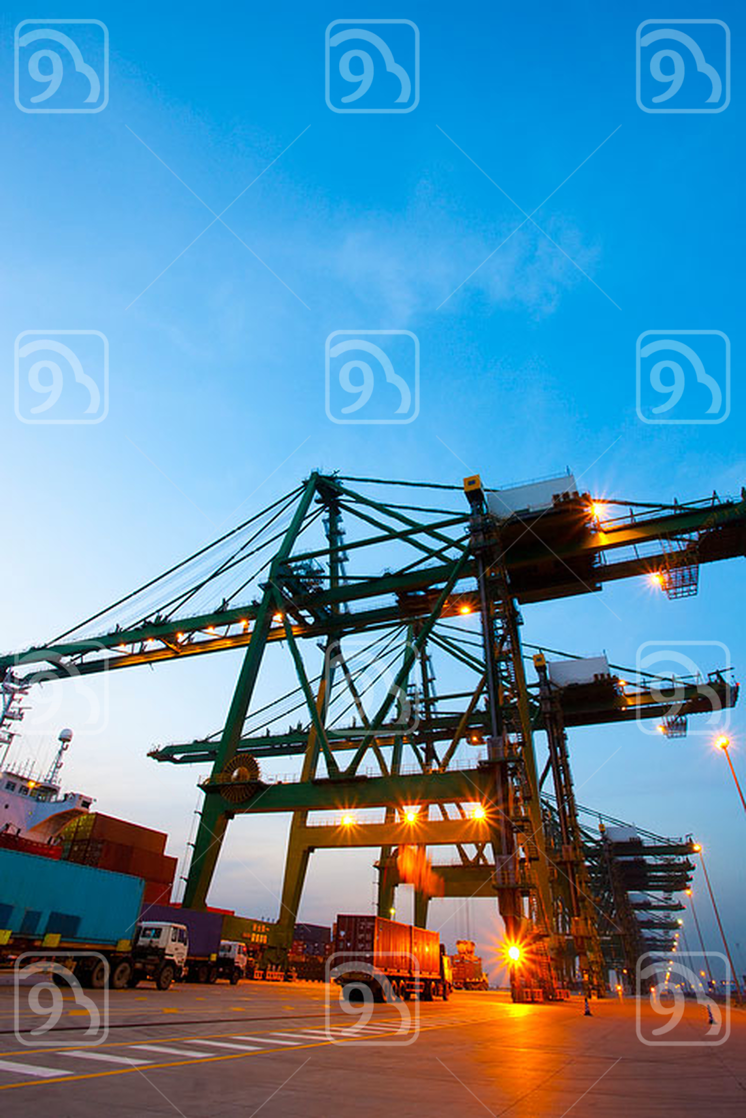 Cranes, cargo containers and trucks at a shipping port during dusk