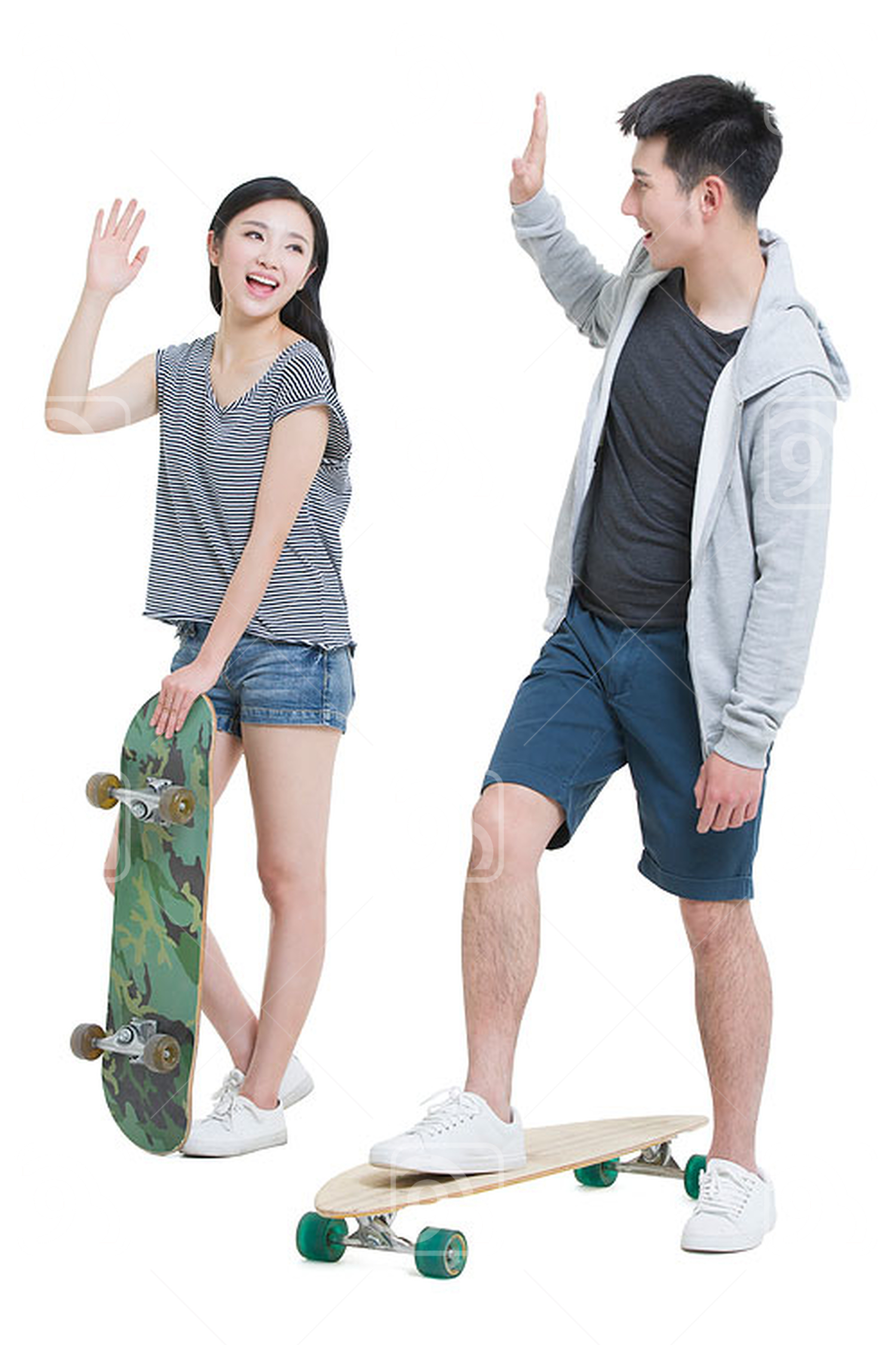 Happy young Chinese couple skateboarding