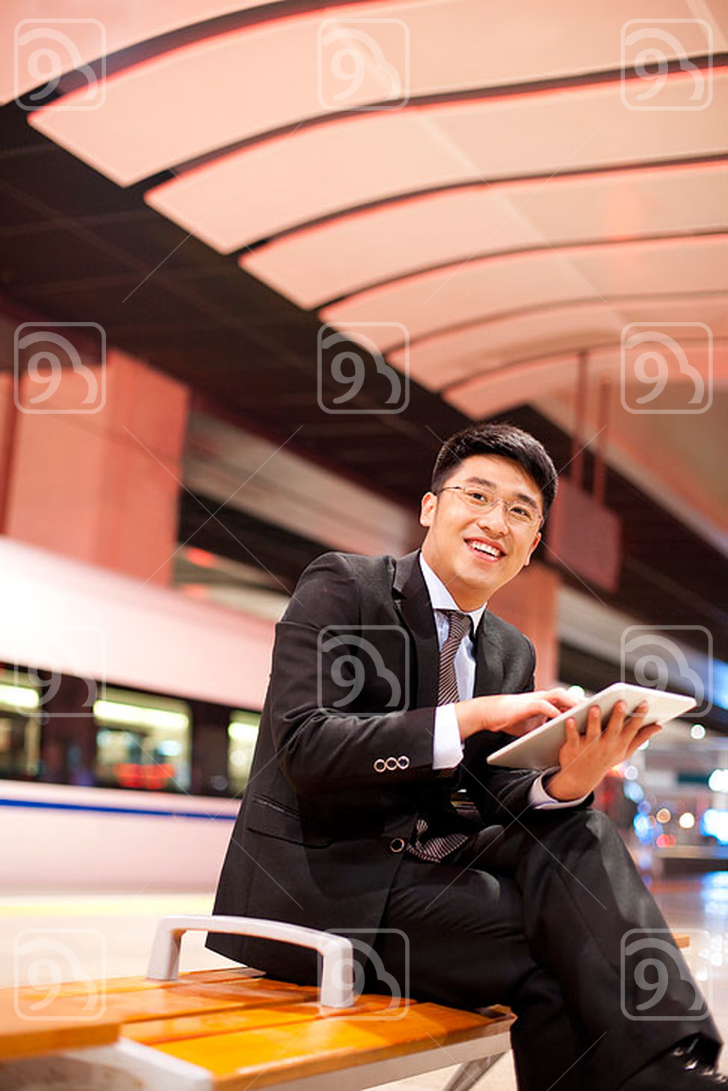 Young Chinese businessman using a digital tablet at the train station