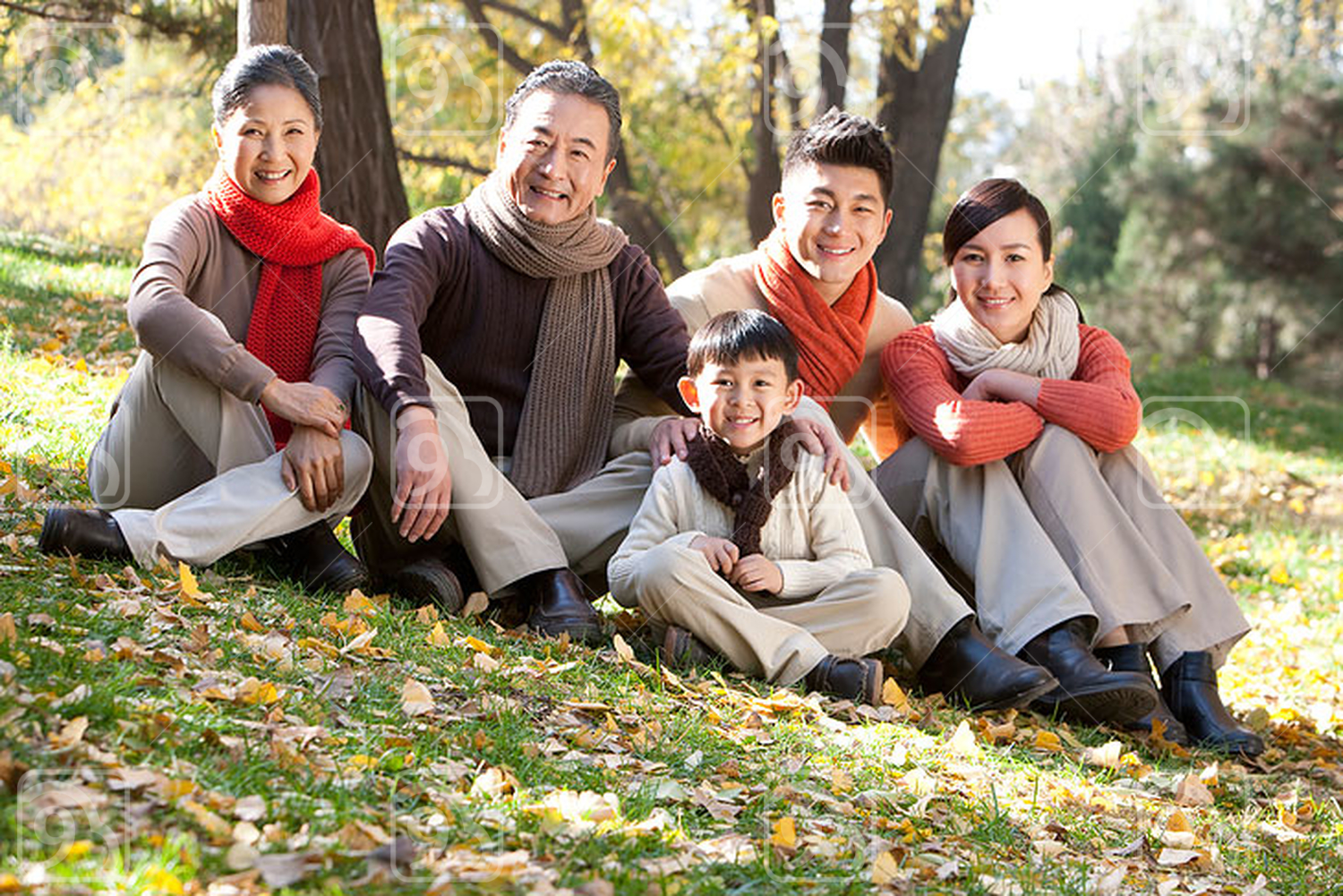 Chinese family sitting on the grass in a park in autumn