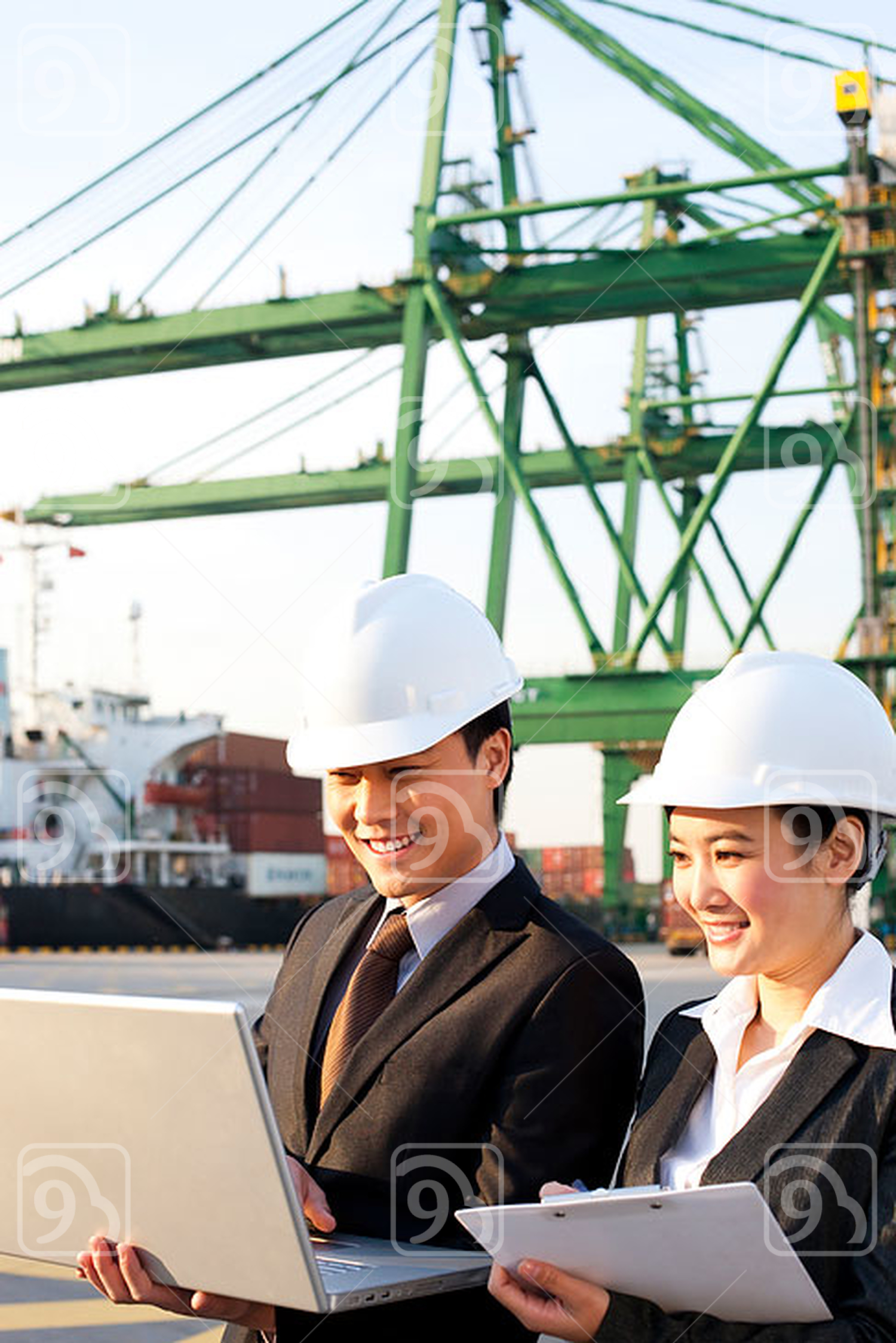 Chinese businesspeople using a laptop at a shipping port