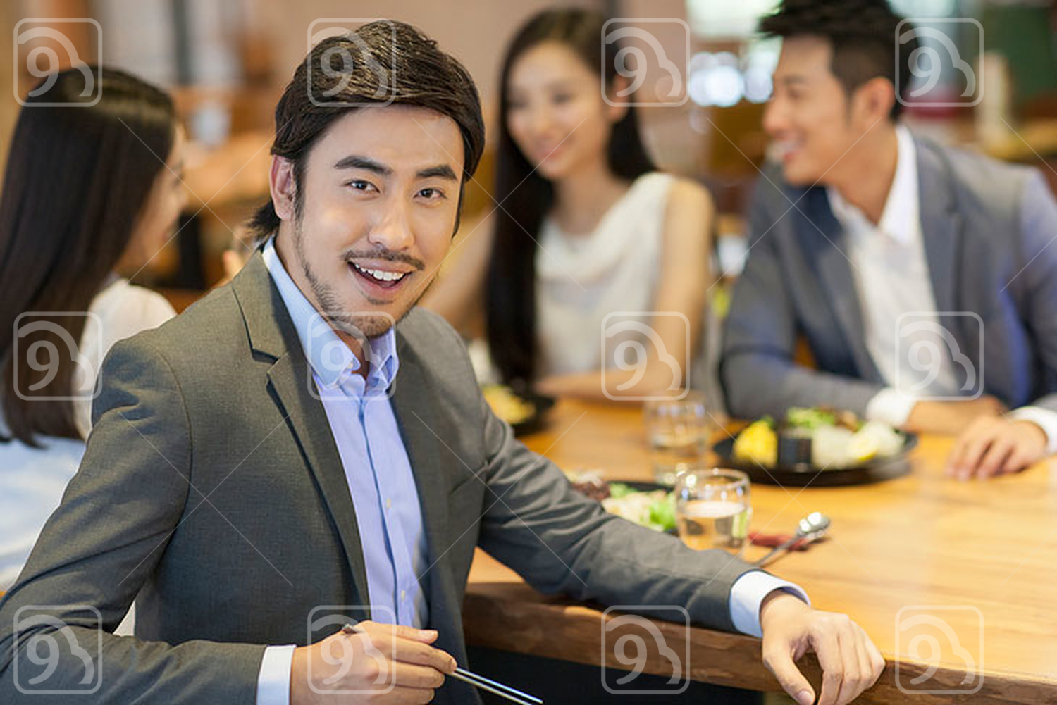 Young Chinese man having dinner with friends