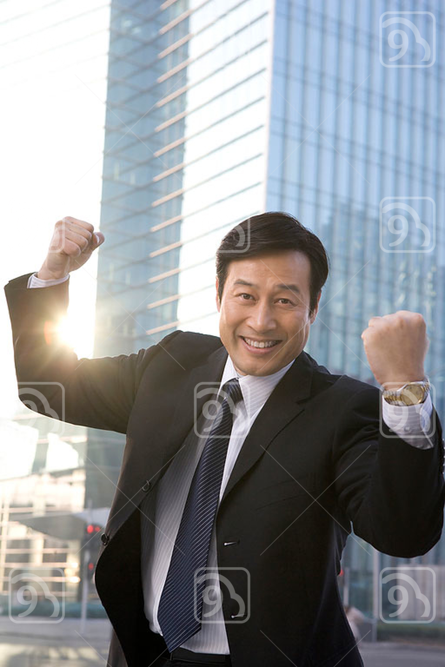 Chinese businessman celebrating in front of office building