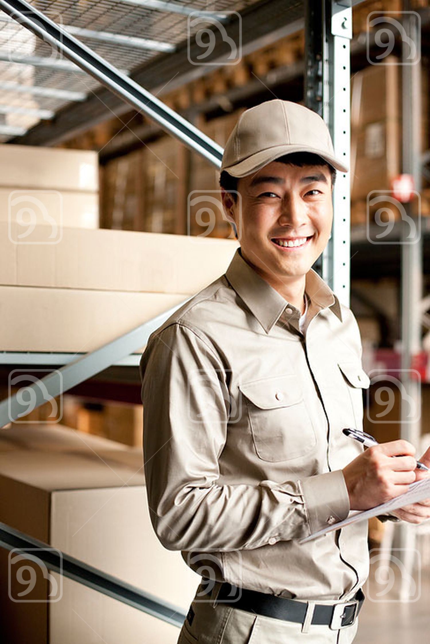 Male Chinese warehouse worker with clipboard