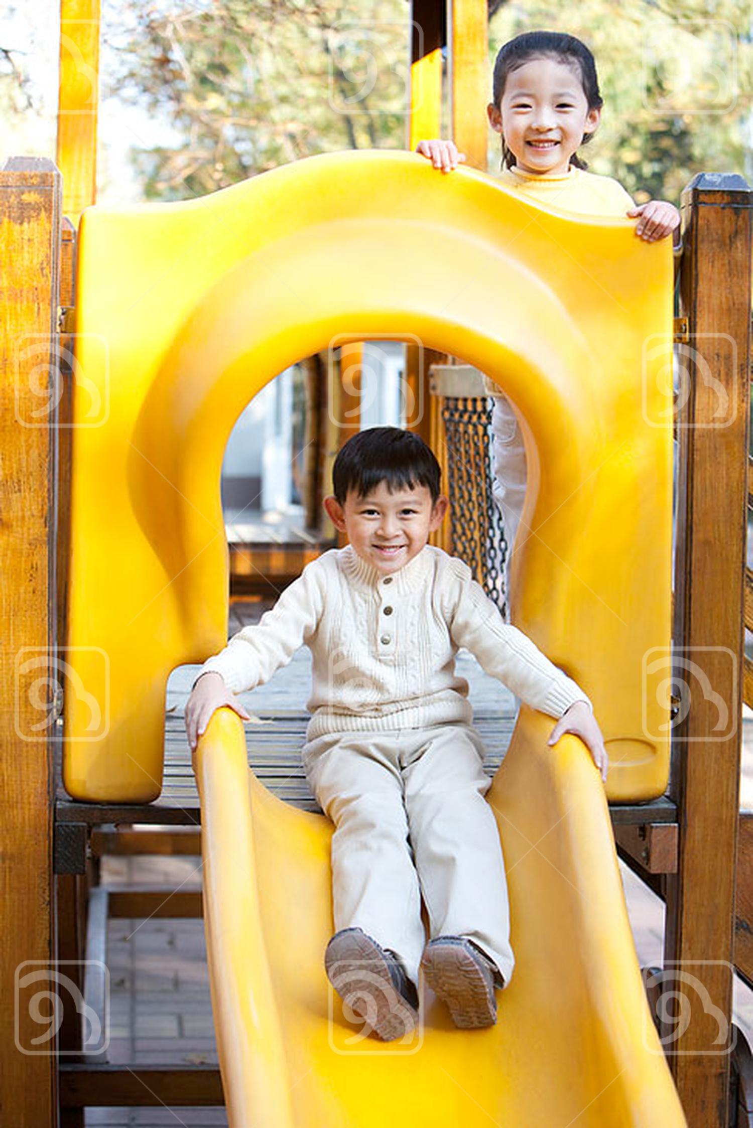 Chinese children playing on playground slide
