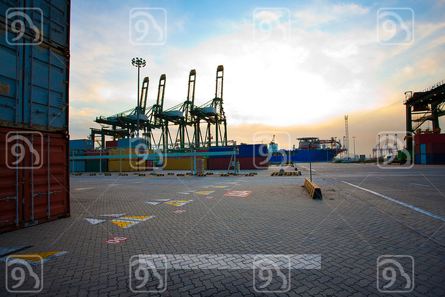 View of cranes, containers and cargo ships at dusk