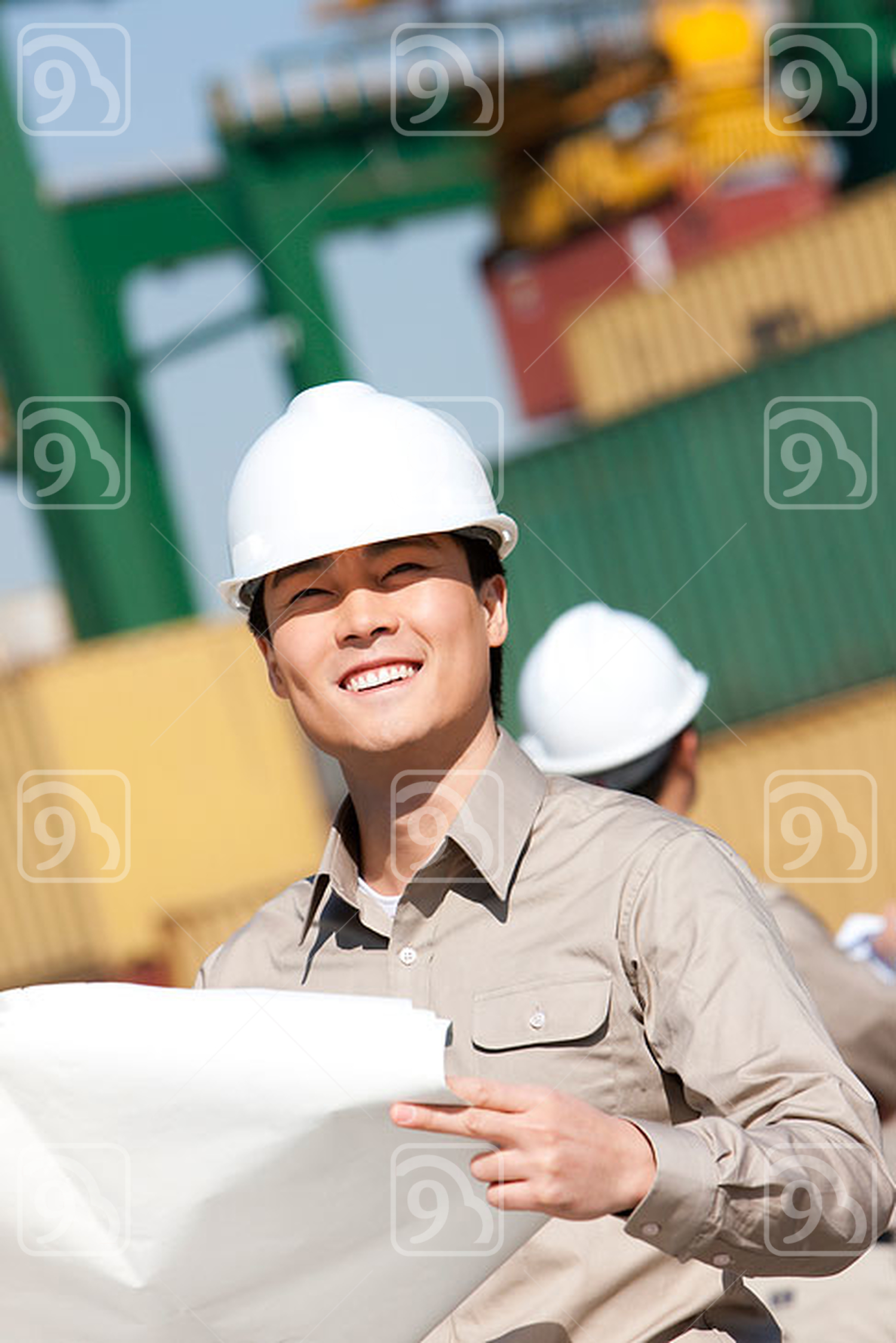 Male Chinese shipping worker checking blueprints