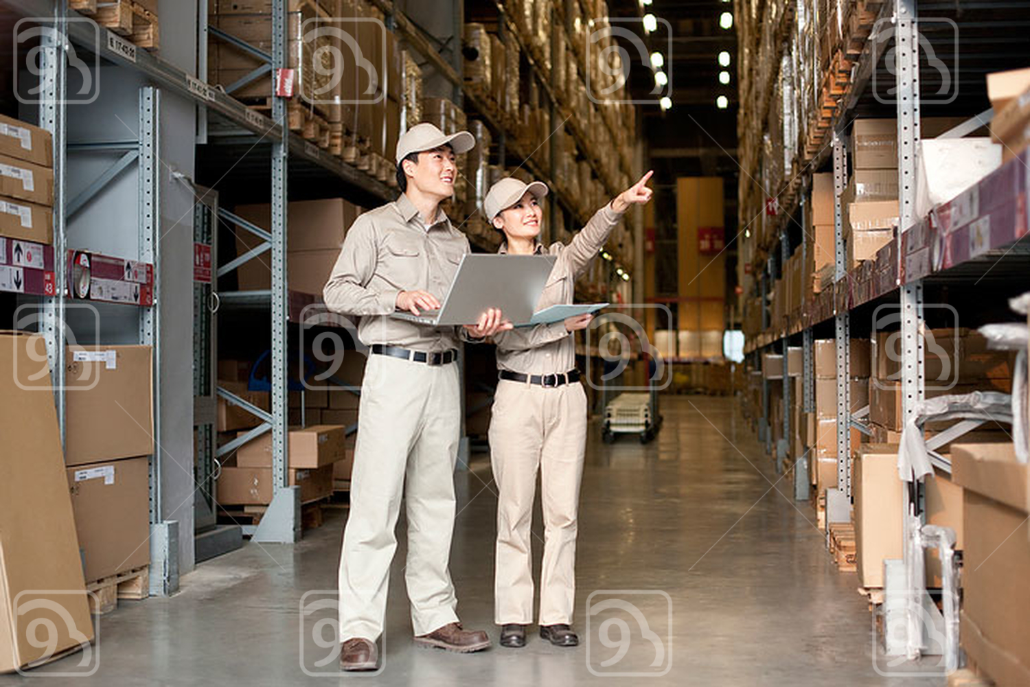 Male and female Chinese warehouse workers with laptop