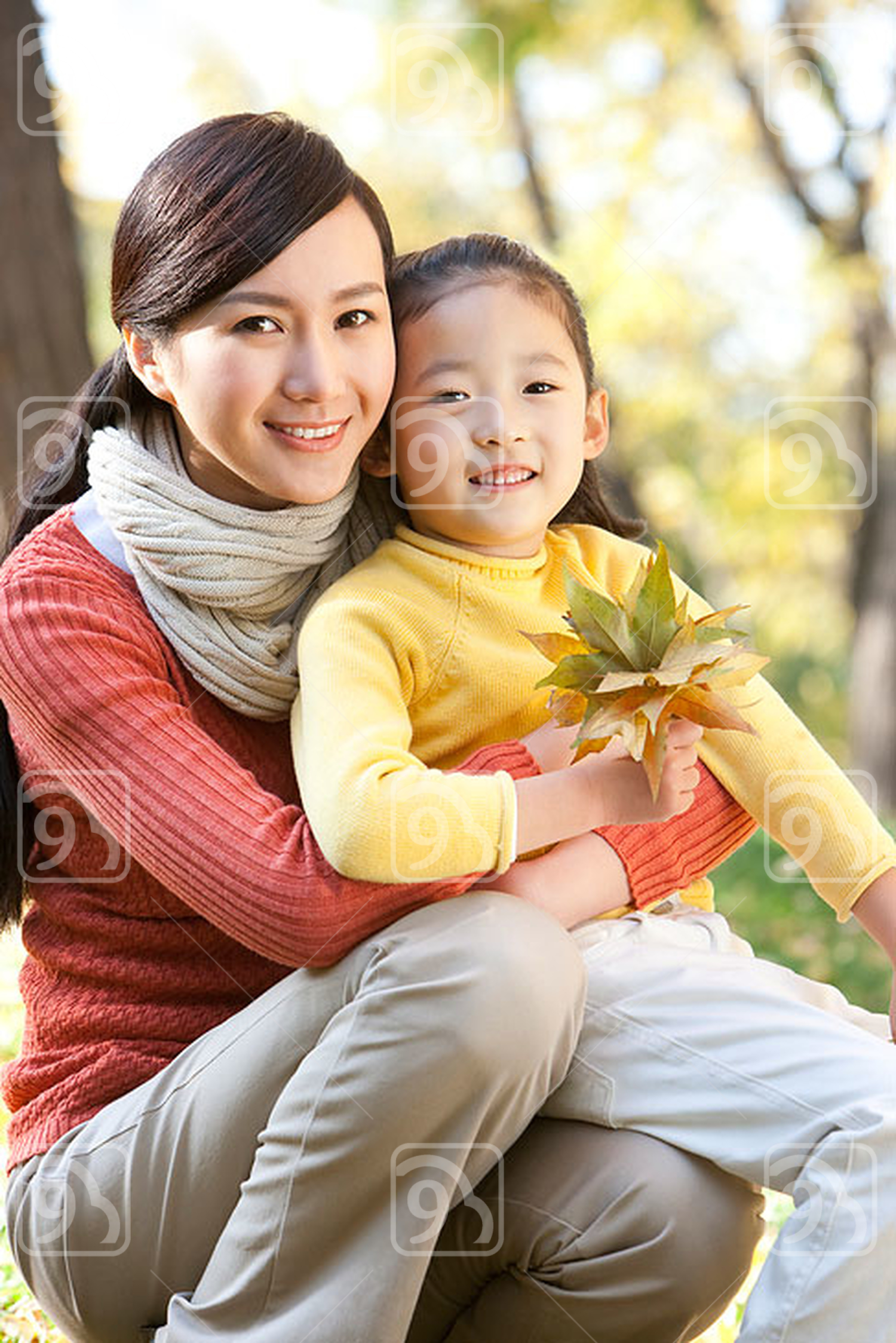 Chinese mother and daughter collecting leaves