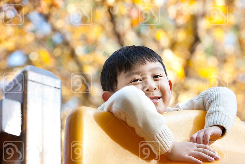 Chinese boy playing on playground slide