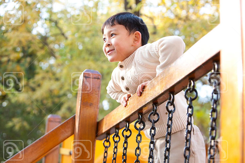 Chinese boy playing on playground toy bridge