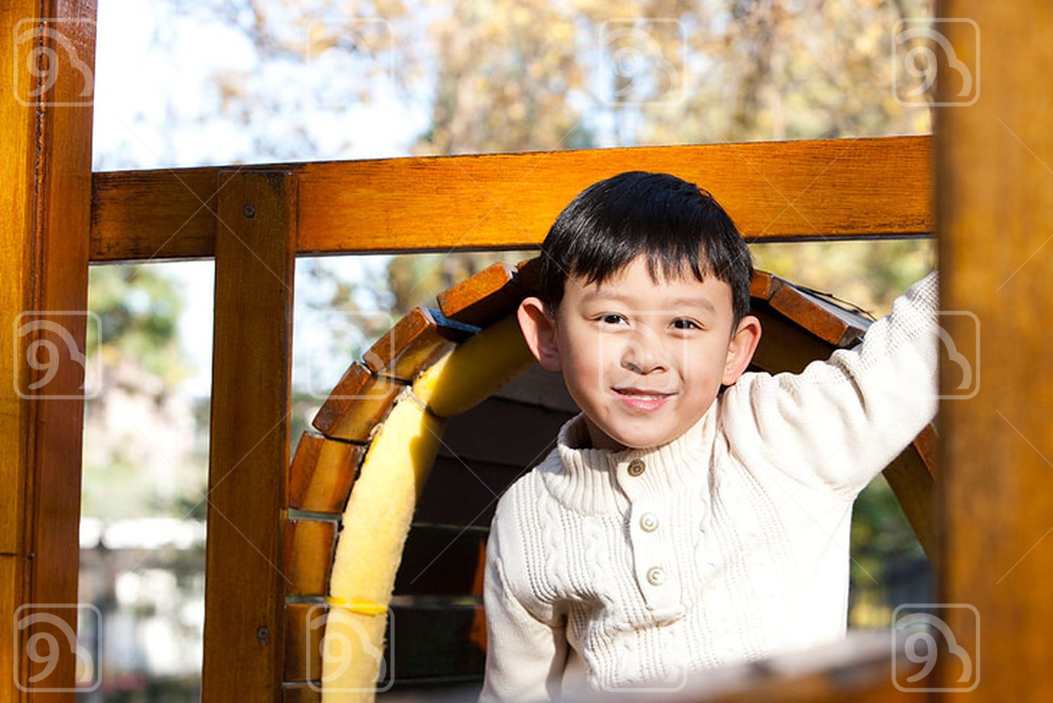 Chinese boy playing on playground toys