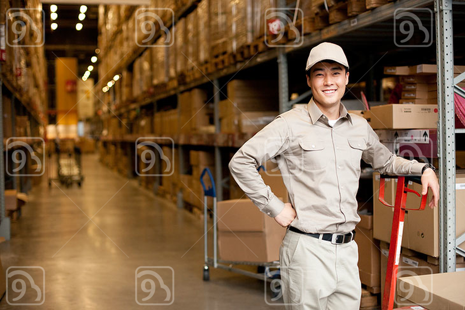 Male Chinese warehouse worker with a pushcart